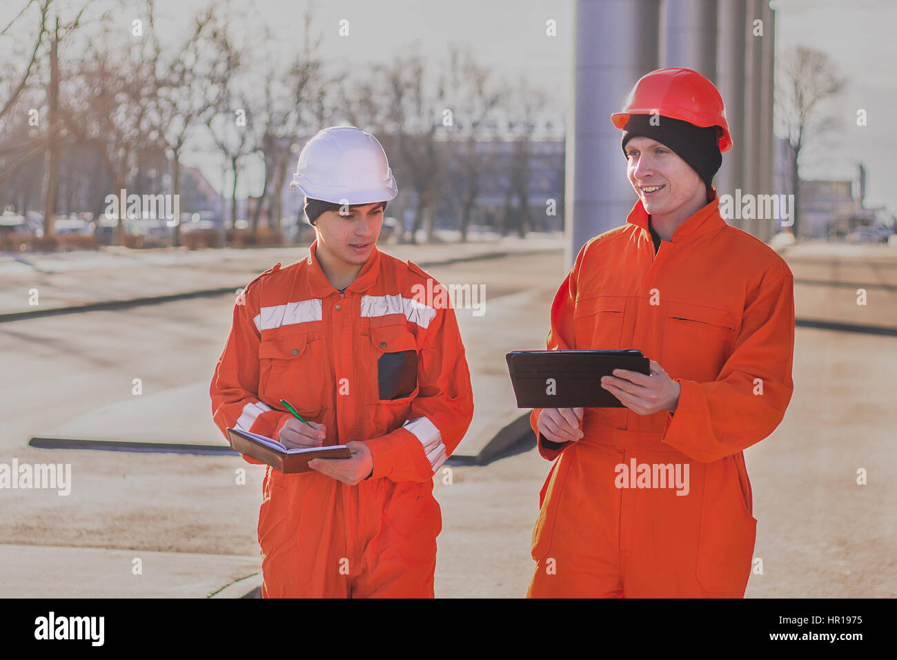 Cheerful young builders in orange uniform with the tablet and notepad. Horizontal outdoors shot. Stock Photo