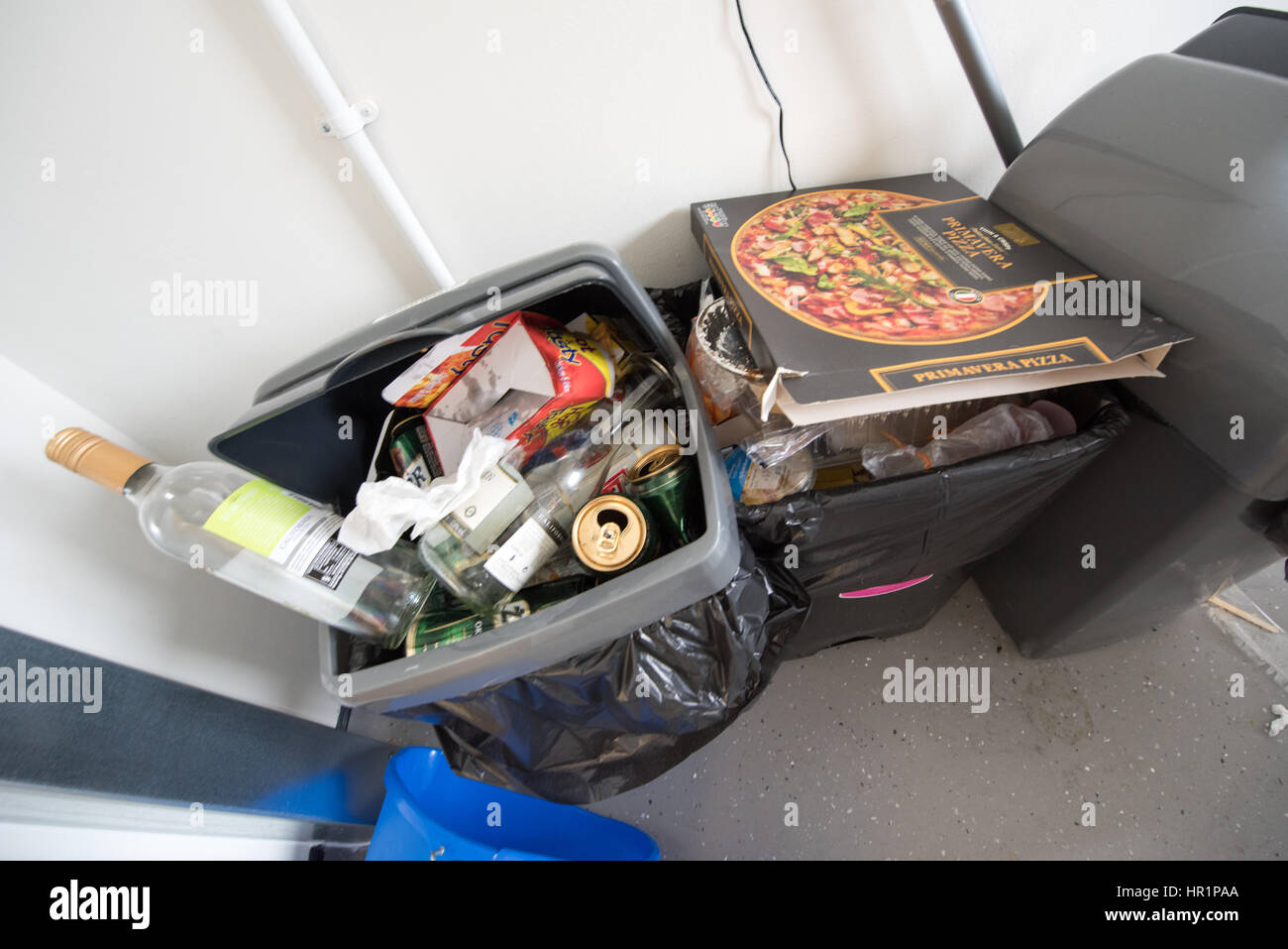Overflowing dirty kitchen plastic swing bins full of rubbish, pizza boxes, wine bottles and beer cans in a student Stock Photo