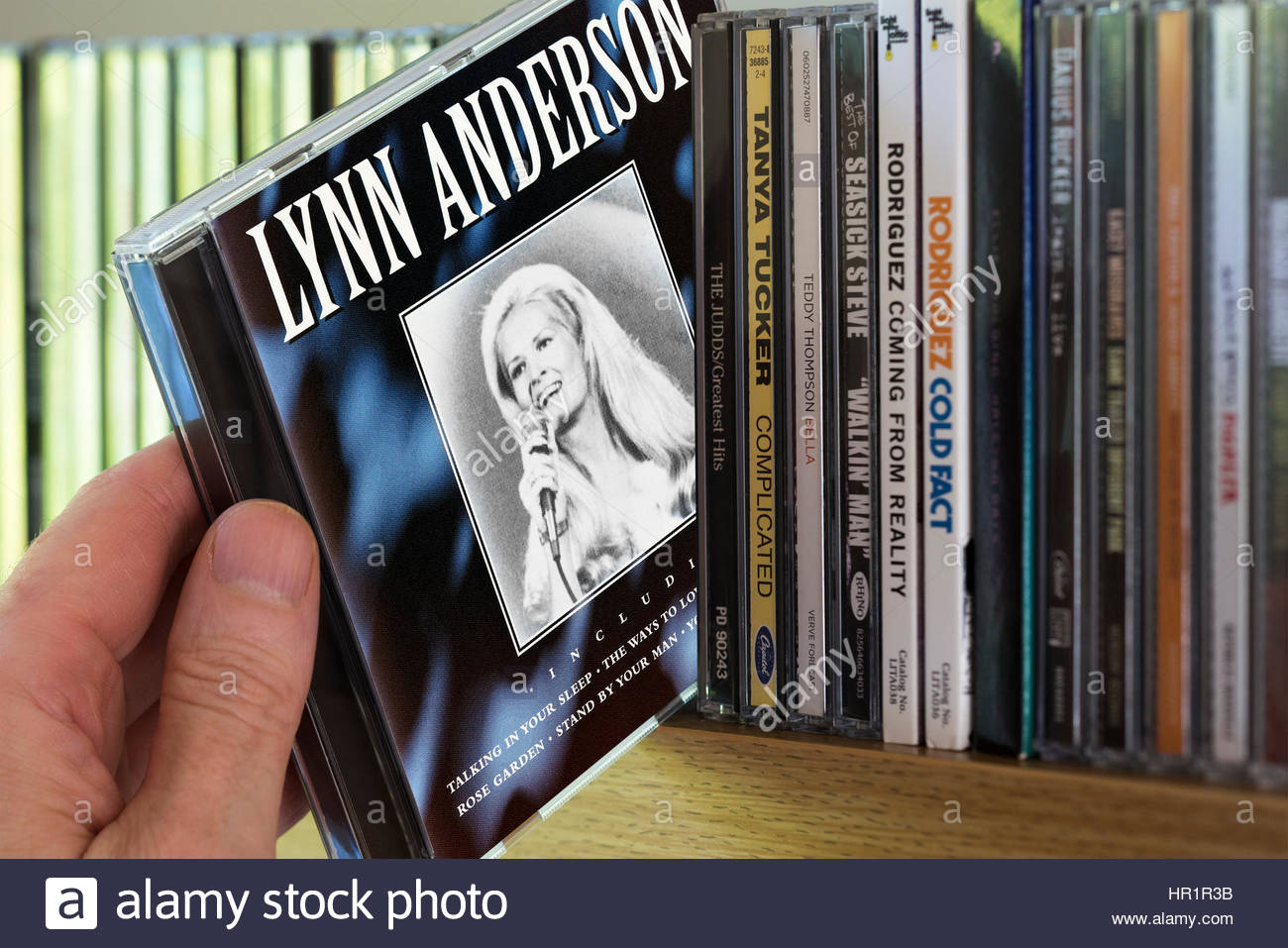 Lynn Anderson CD being chosen from a shelf of other CD's, England - Stock Image