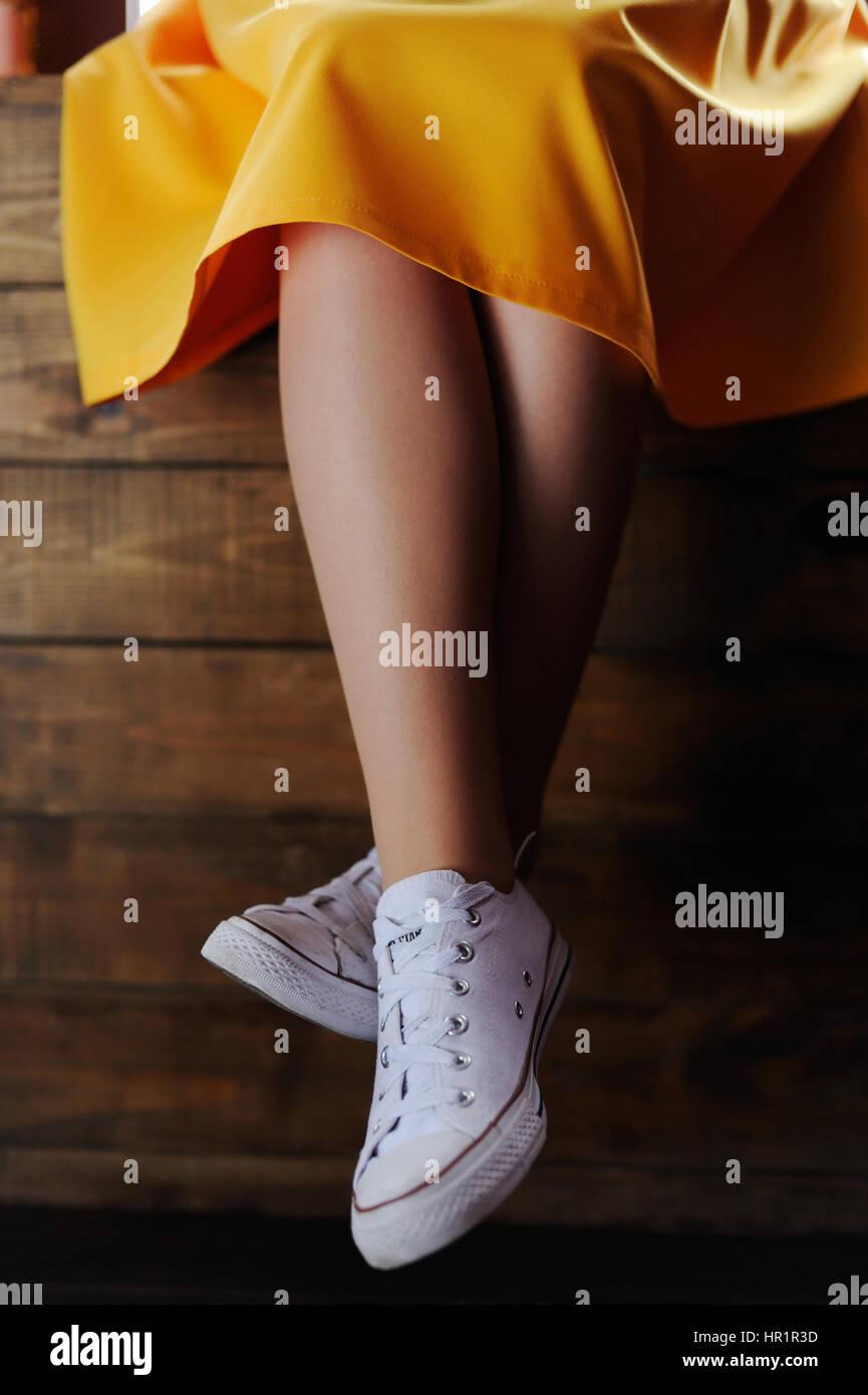 Wearing in converse girls leg on dark background - Stock Image