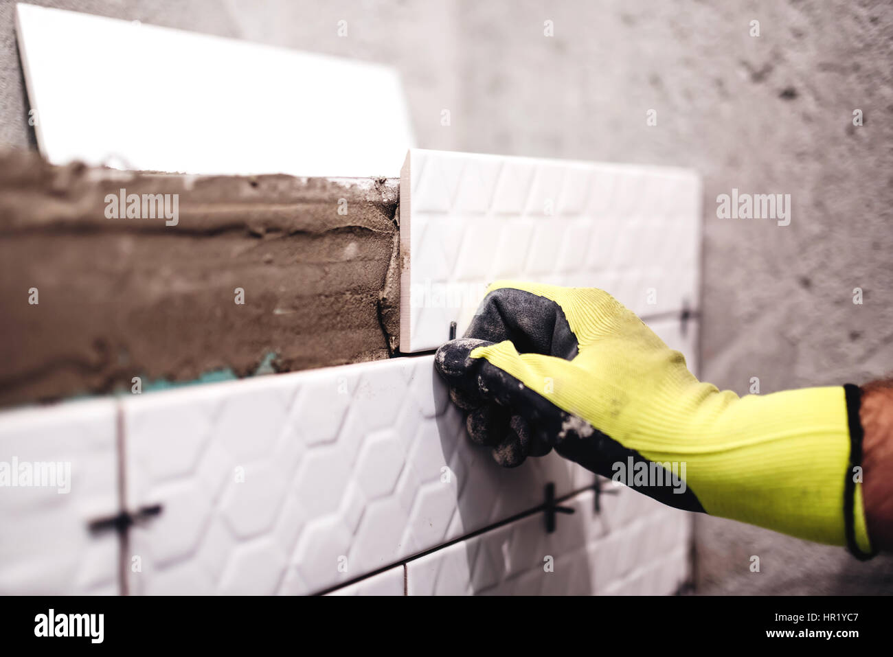 handy man, tiler applying ceramics with adhesive and using plastic spacers in interior design manufacturing - Stock Image