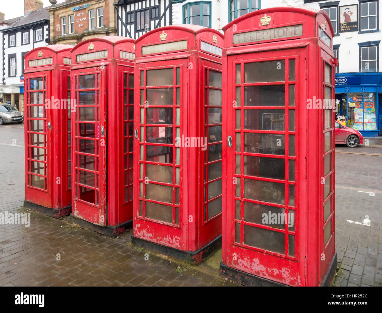 Four classic red British 'K6' type telephone boxes collectively grade 2 listed Ripon Market Place - Stock Image