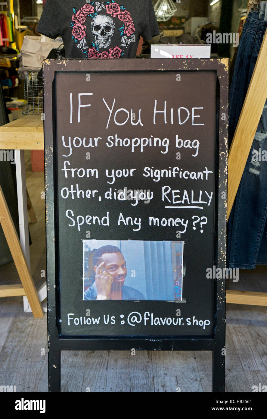 A funny sign inside a women's clothing store in Cobble Hill Brooklyn encouraging women to shop and hide their - Stock Image