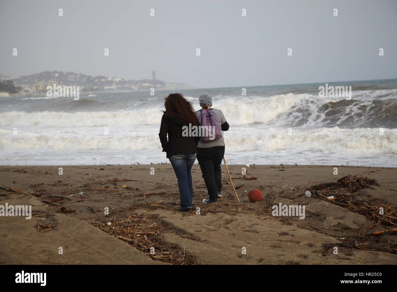 Two girls looking att  big waves in the beach of Malaga. - Stock Image