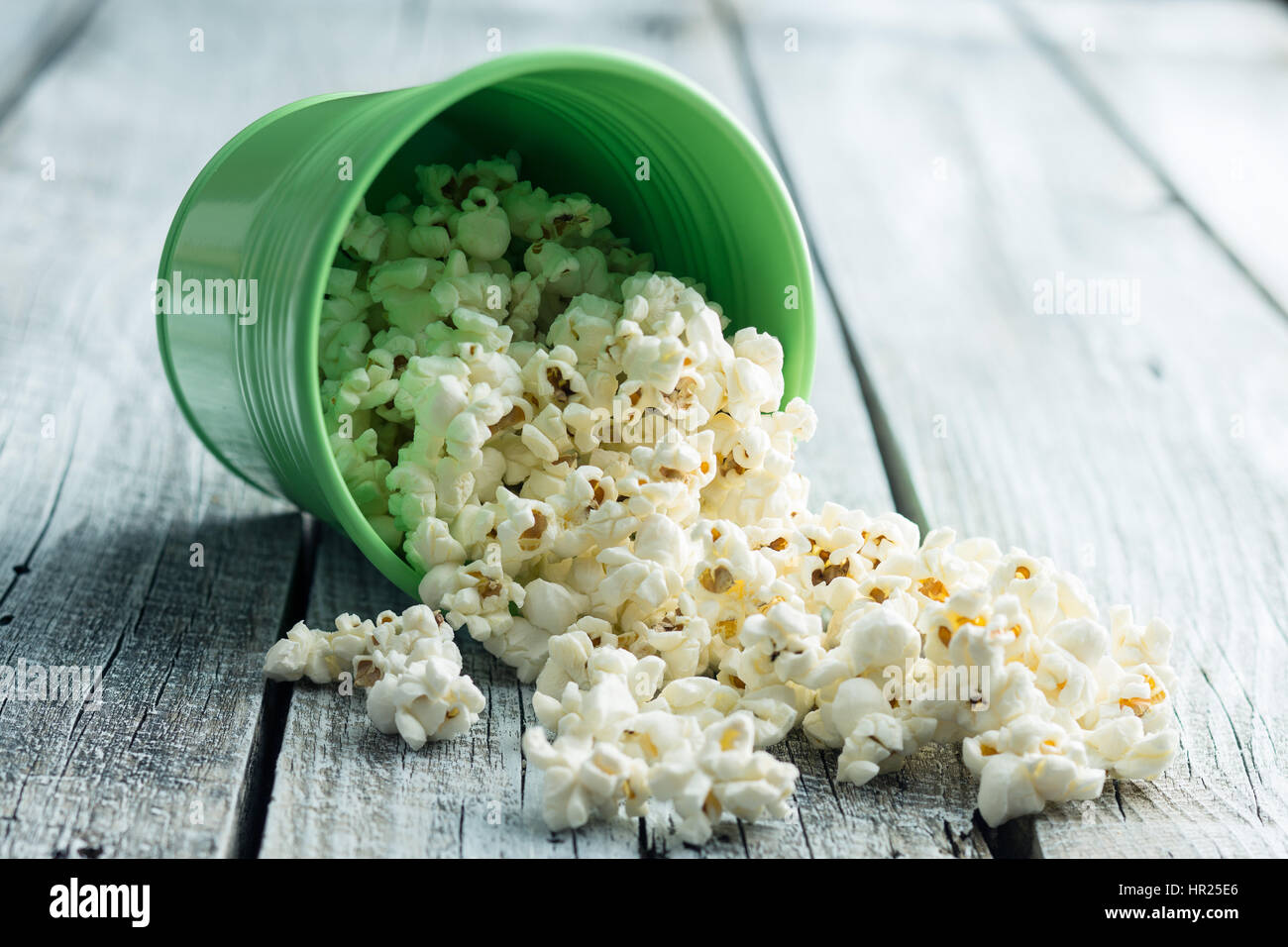 The salty popcorn on old wooden table. - Stock Image