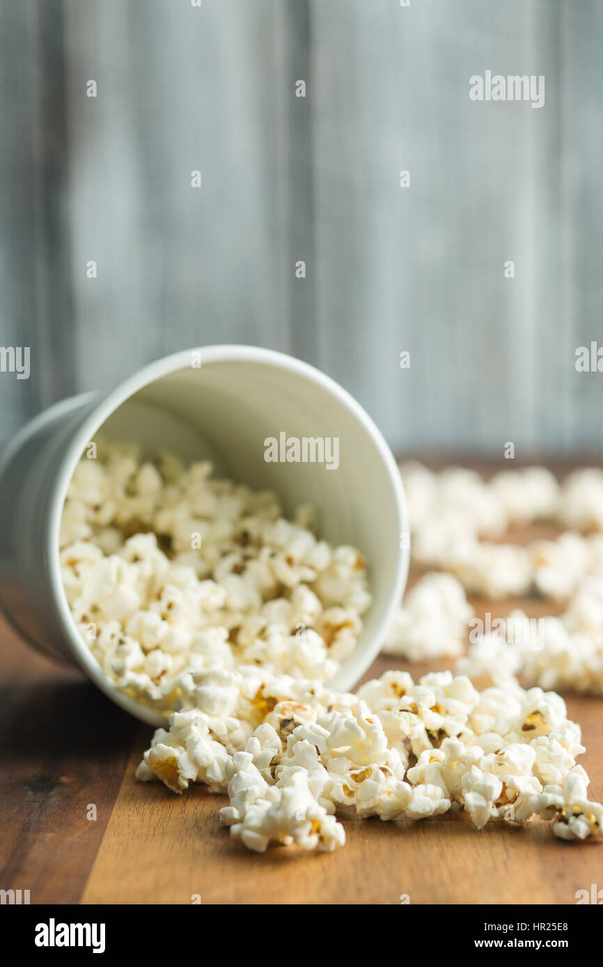 The salty popcorn on wooden table. - Stock Image