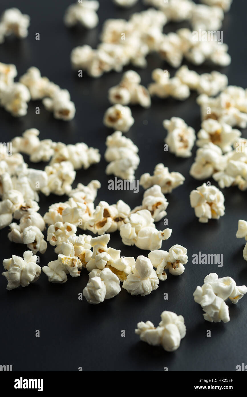 The salty popcorn on black background. - Stock Image
