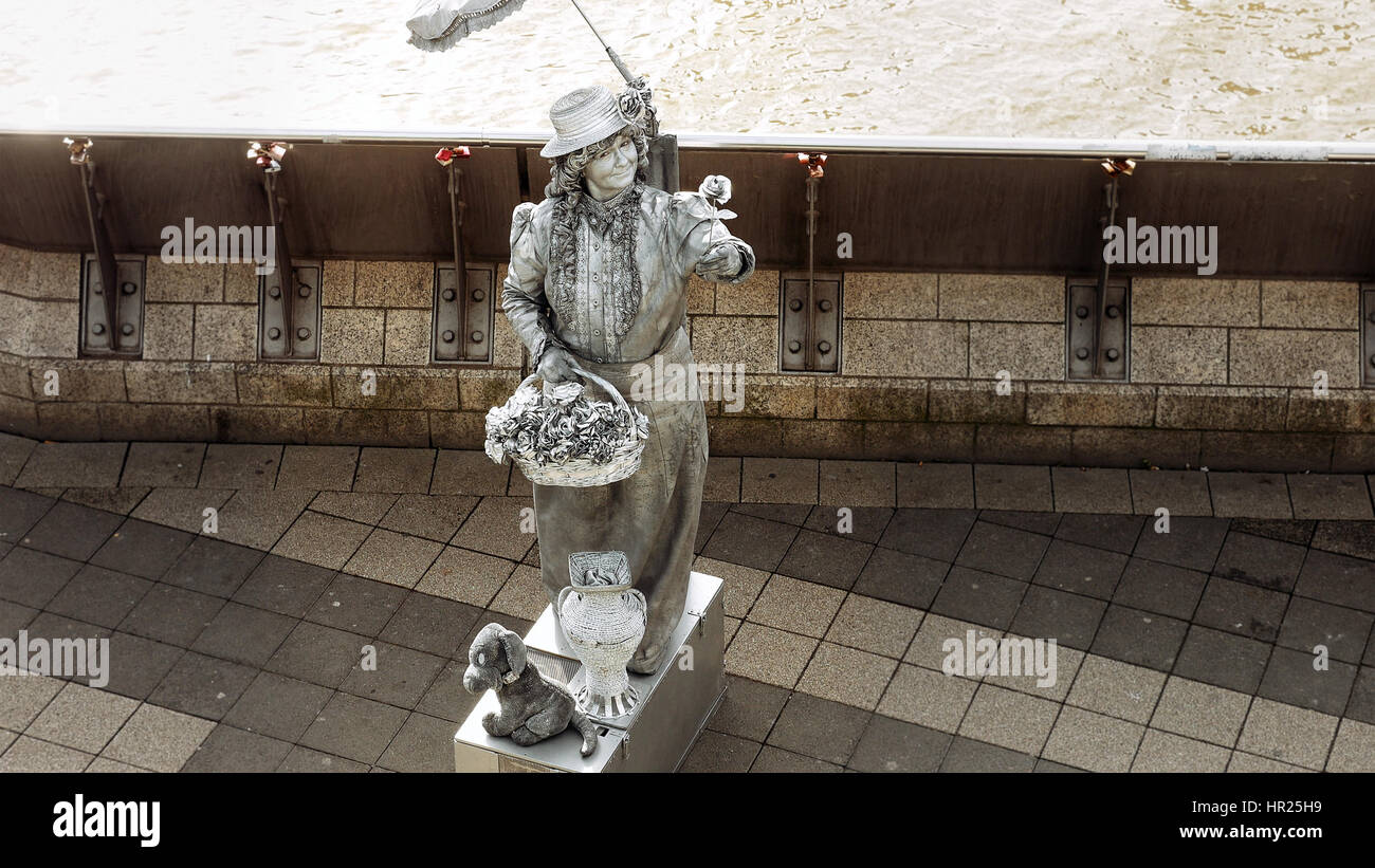 Hamburg, Germany - October, 10, 2016: Living statue street performer in Hamburg port poses to attract tourists and - Stock Image
