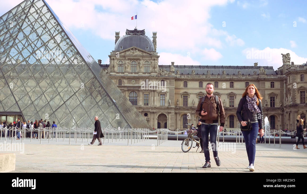 Paris, France - October, 14, 2016: Multiracial tourists walking near glass pyramid in Louvre palace courtyard. Louvre - Stock Image