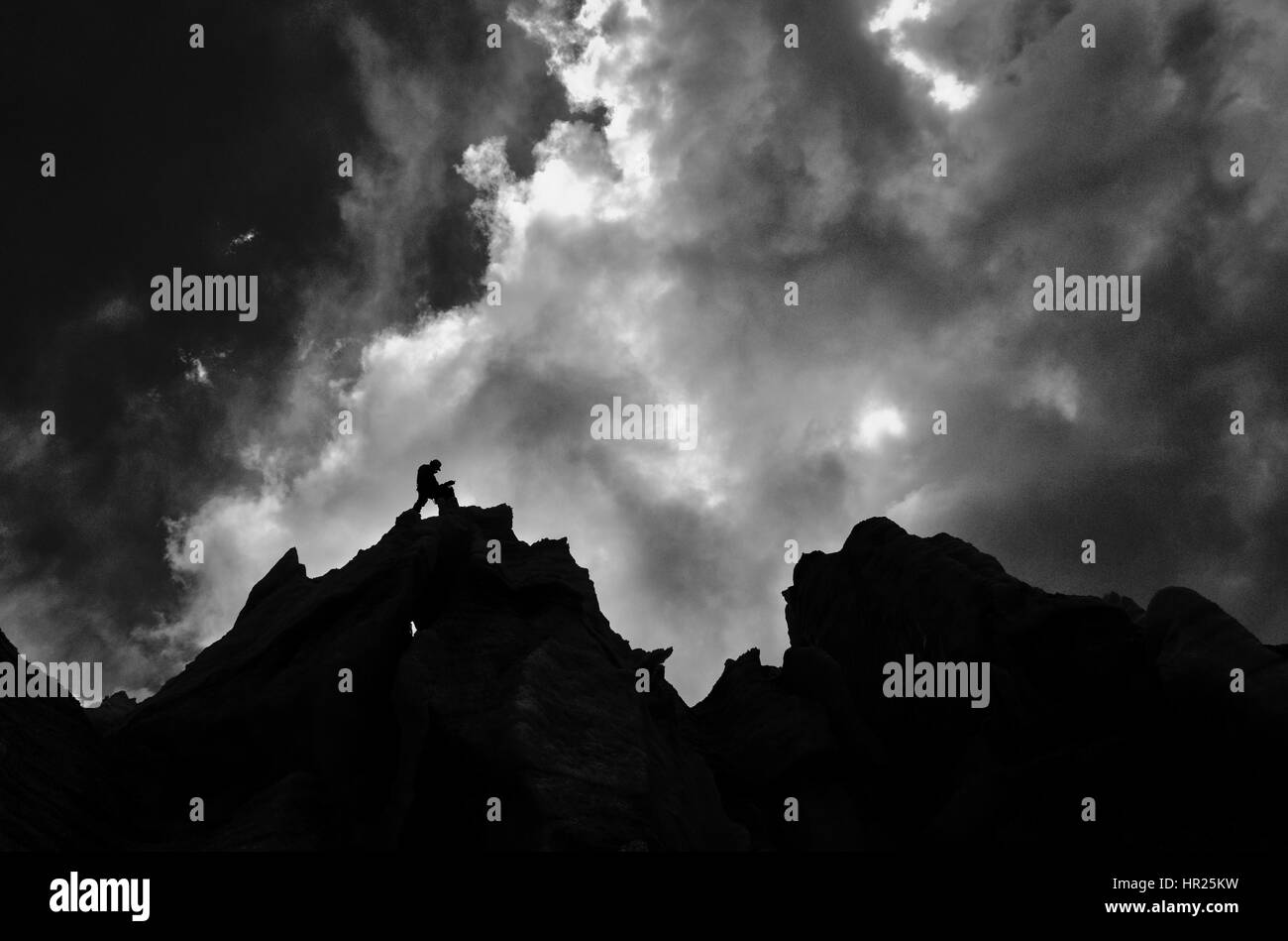 Dramatic lighting on a climber coiling rope at the top of a climb - Stock Image