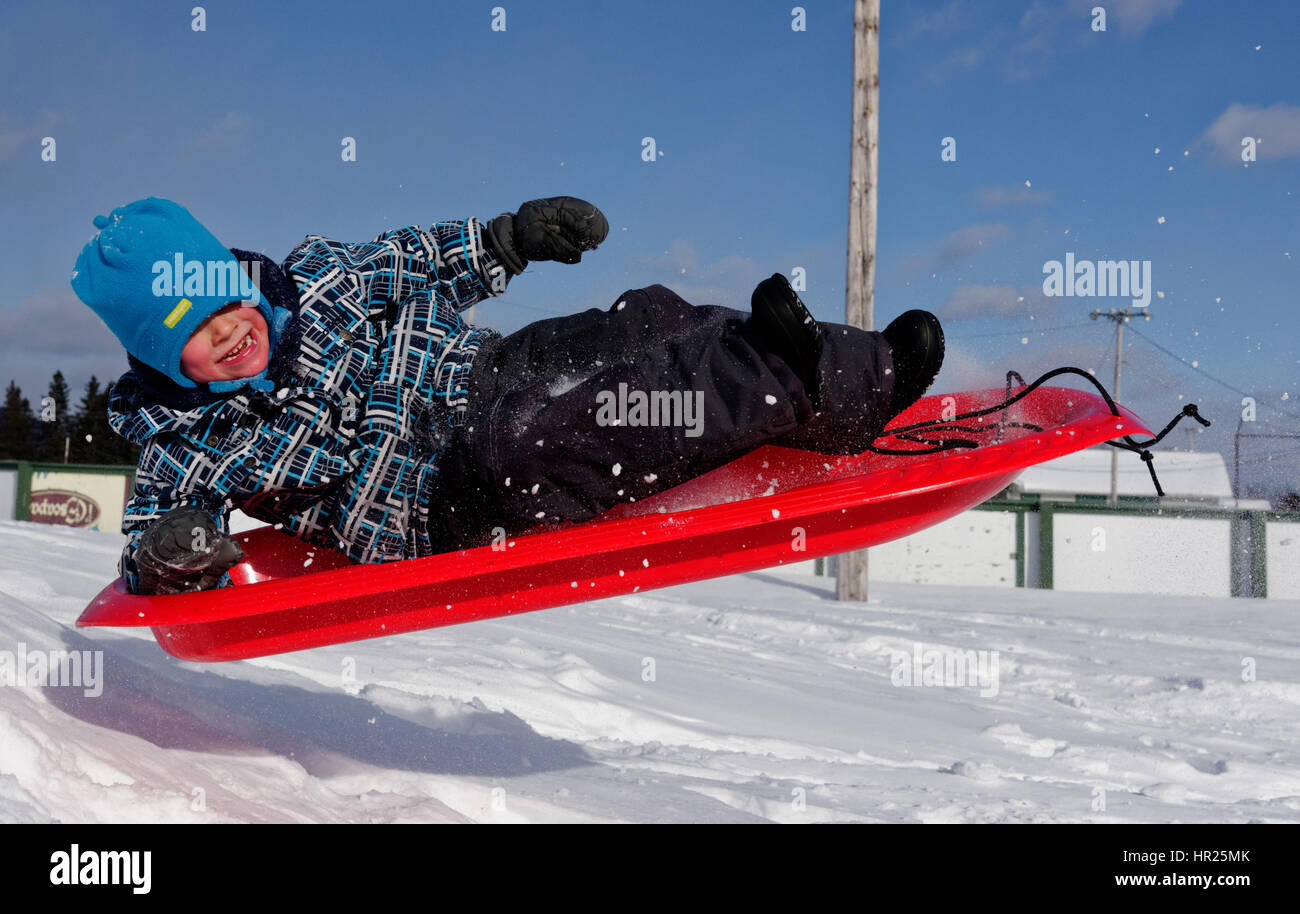 A young Boy (4 yrs old) jumping into the air on a sledge in Quebec winter - Stock Image