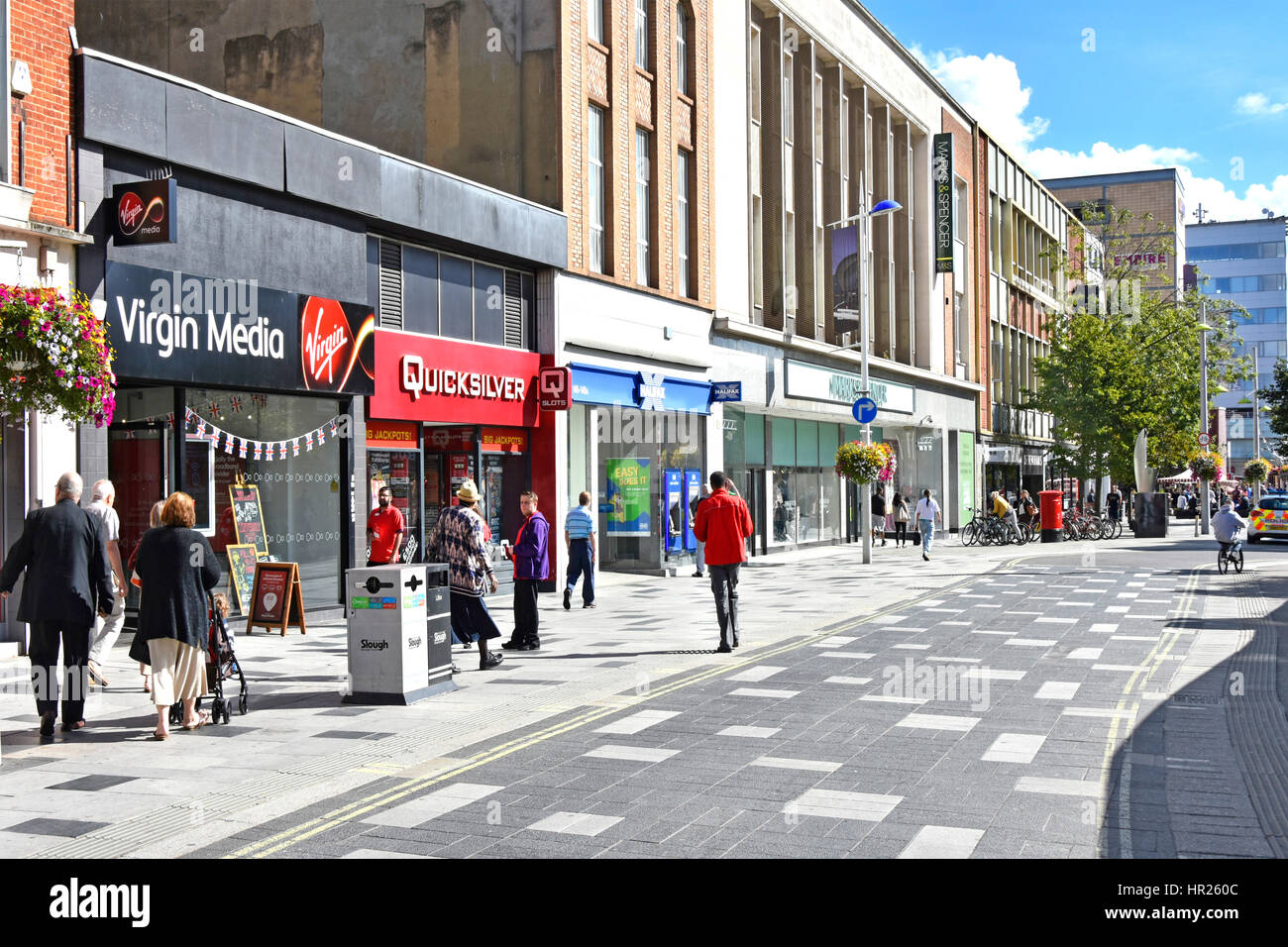 Shoppers high street retail shopping area in town centre Slough Berkshire UK paved-over road prioritised for pedestrians - Stock Image