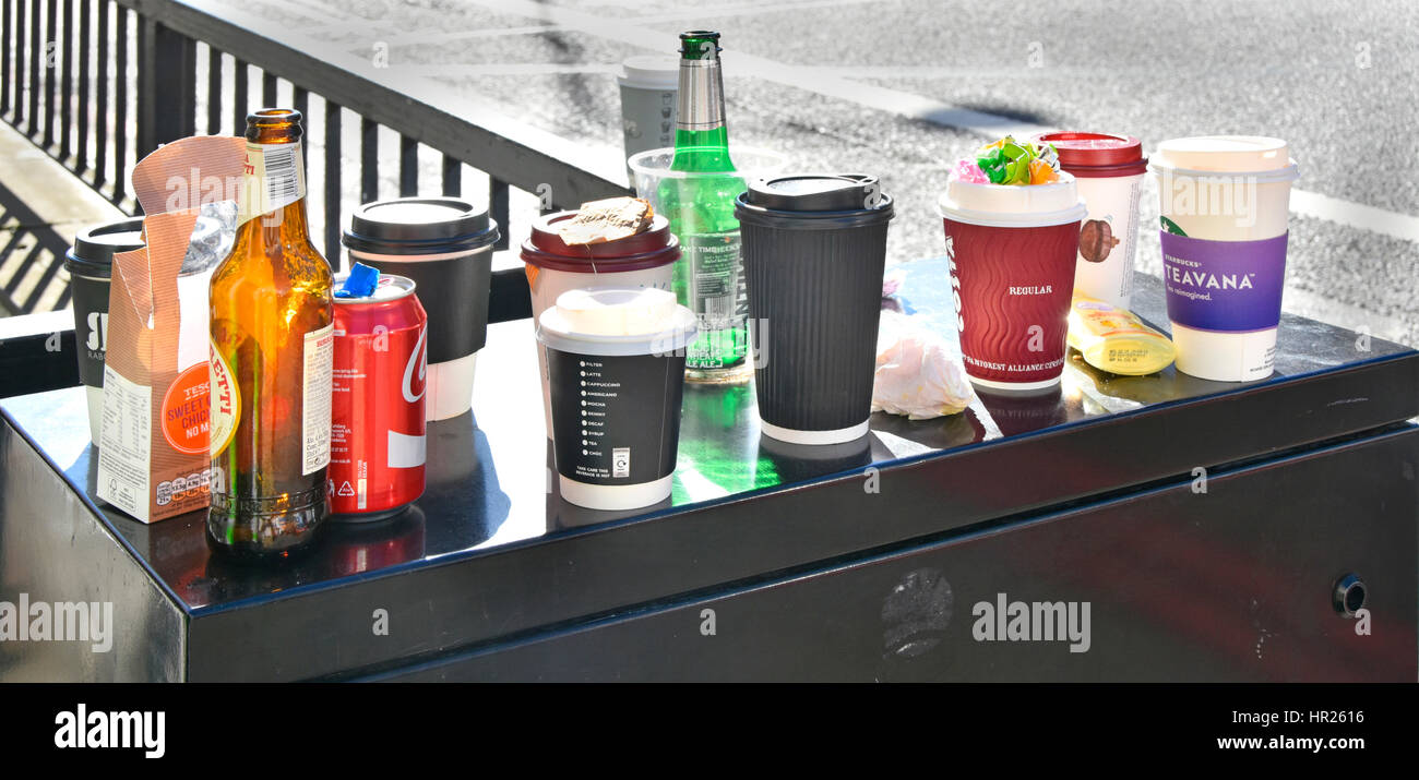 Rubbish left from lunch break office workers after snacking in street beer bottle paper cups coffee cup cans garbage - Stock Image