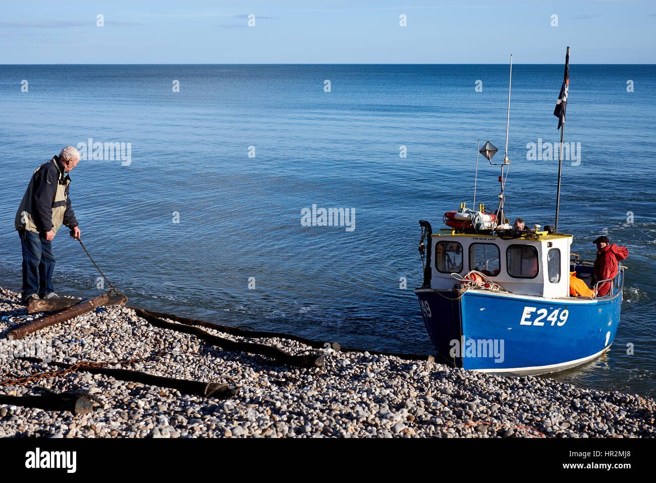 Hauling a fishing boat back on to the shore at Beer in Devon, U.K. Stock Photo