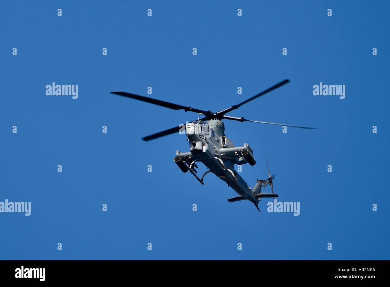 AH-1W Super Cobra attack helicopter used by US Marines, in flight over San Diego Harbor, California. Stock Photo