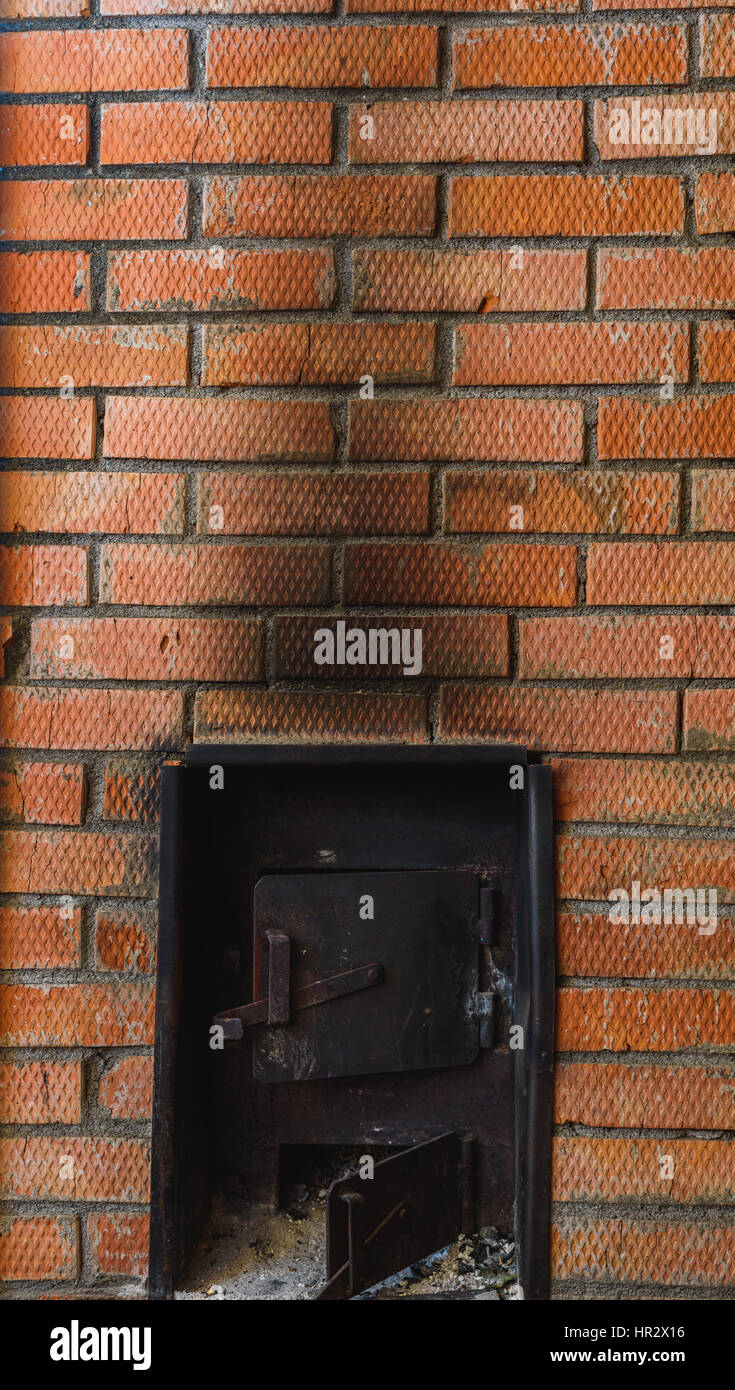iron stove in the Russian sauna lined with red brick - Stock Image