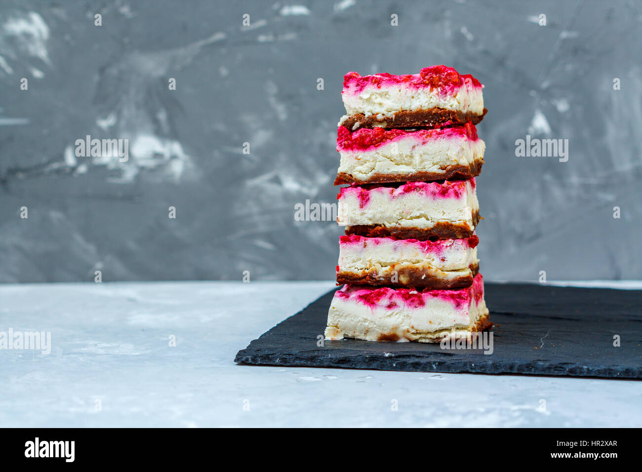 Vegan raw raspberry cheesecake on a dark background. Love for a healthy vegan food concept - Stock Image