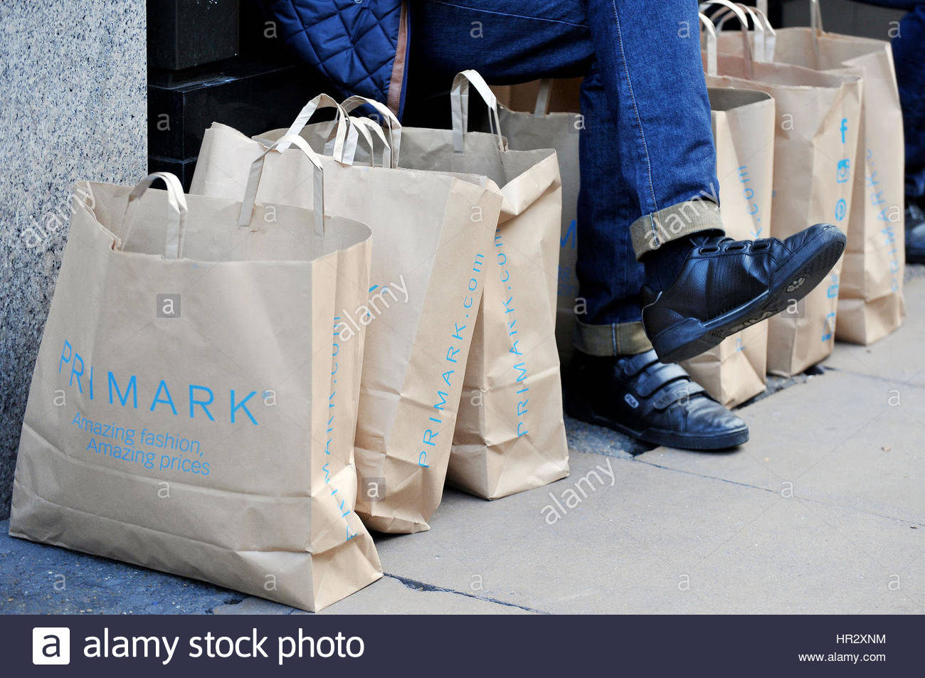 File photo dated 04/11/14 of a man surrounded by Primark bags in London, as Primark owner Associated British Foods - Stock Image
