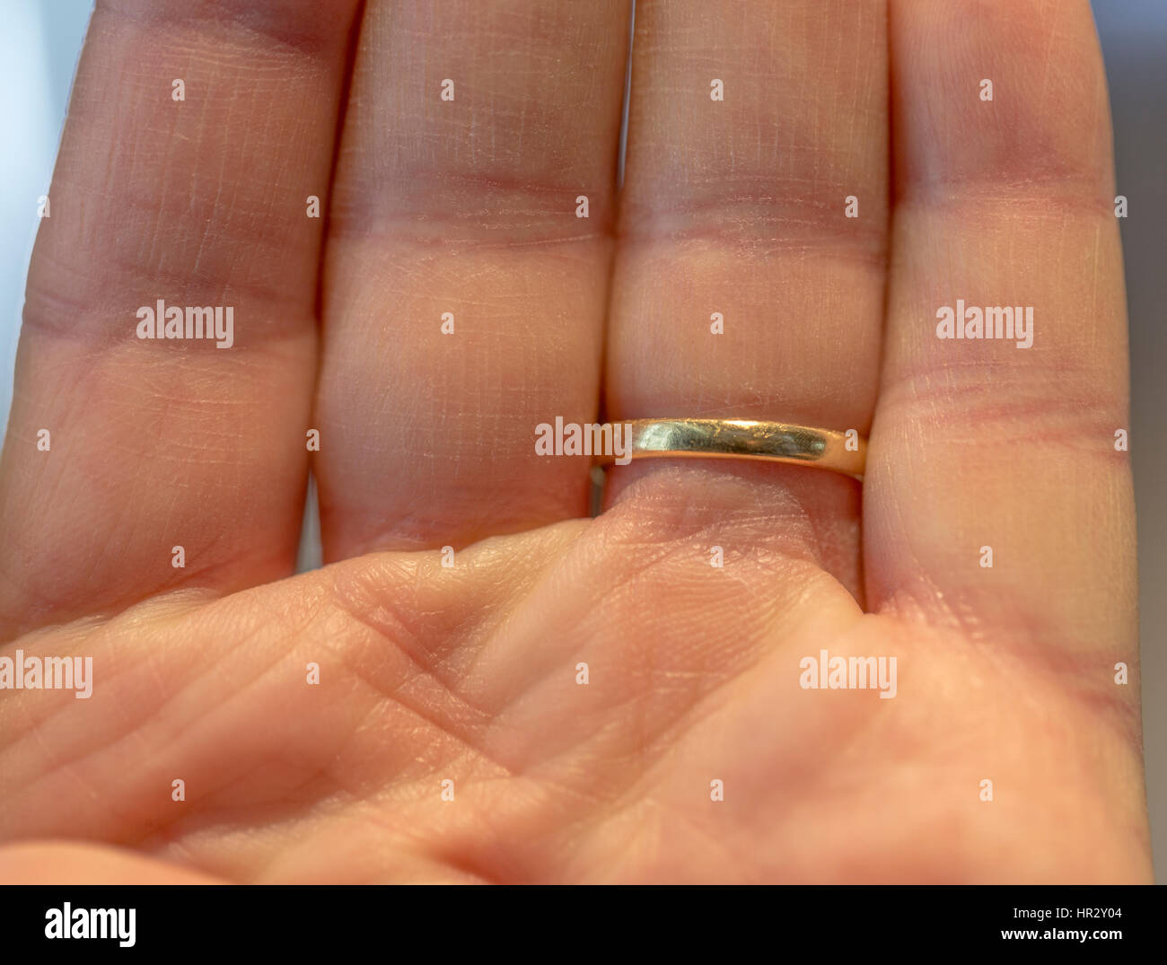 Man's outstretched fingers wearing a gold wedding ring - Stock Image