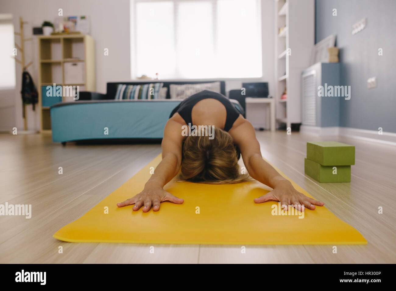 Woman doing stretching exercise on yoga mat. Fitness female performing yoga on exercise mat at gym. Child Pose, Stock Photo