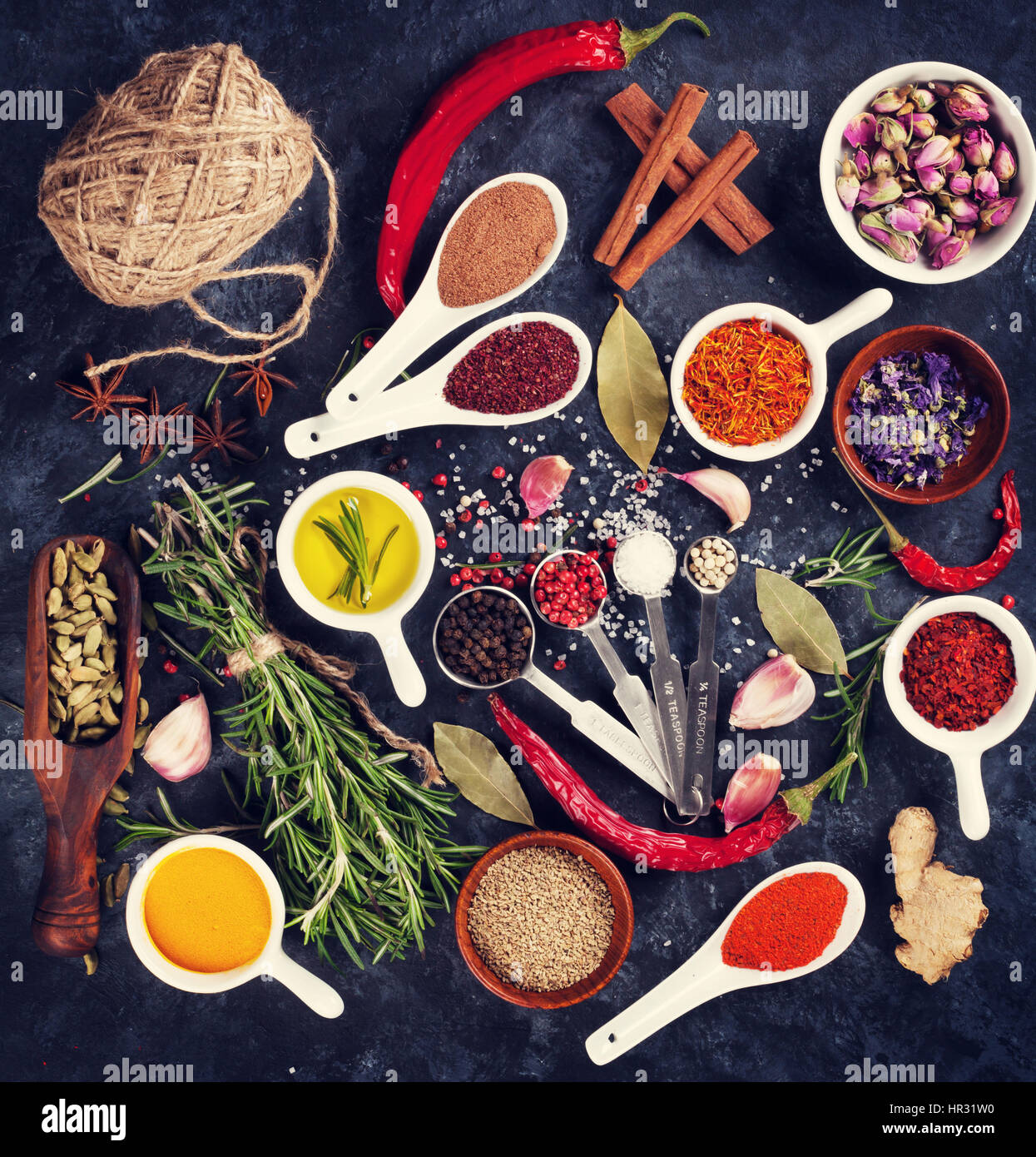 Herbs and spices over black stone background. Top view. Retro toned - Stock Image