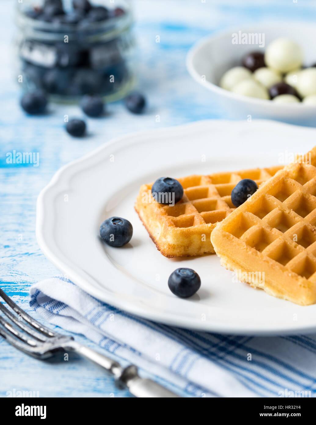 Belgian waffles on white plate on light blue background. - Stock Image