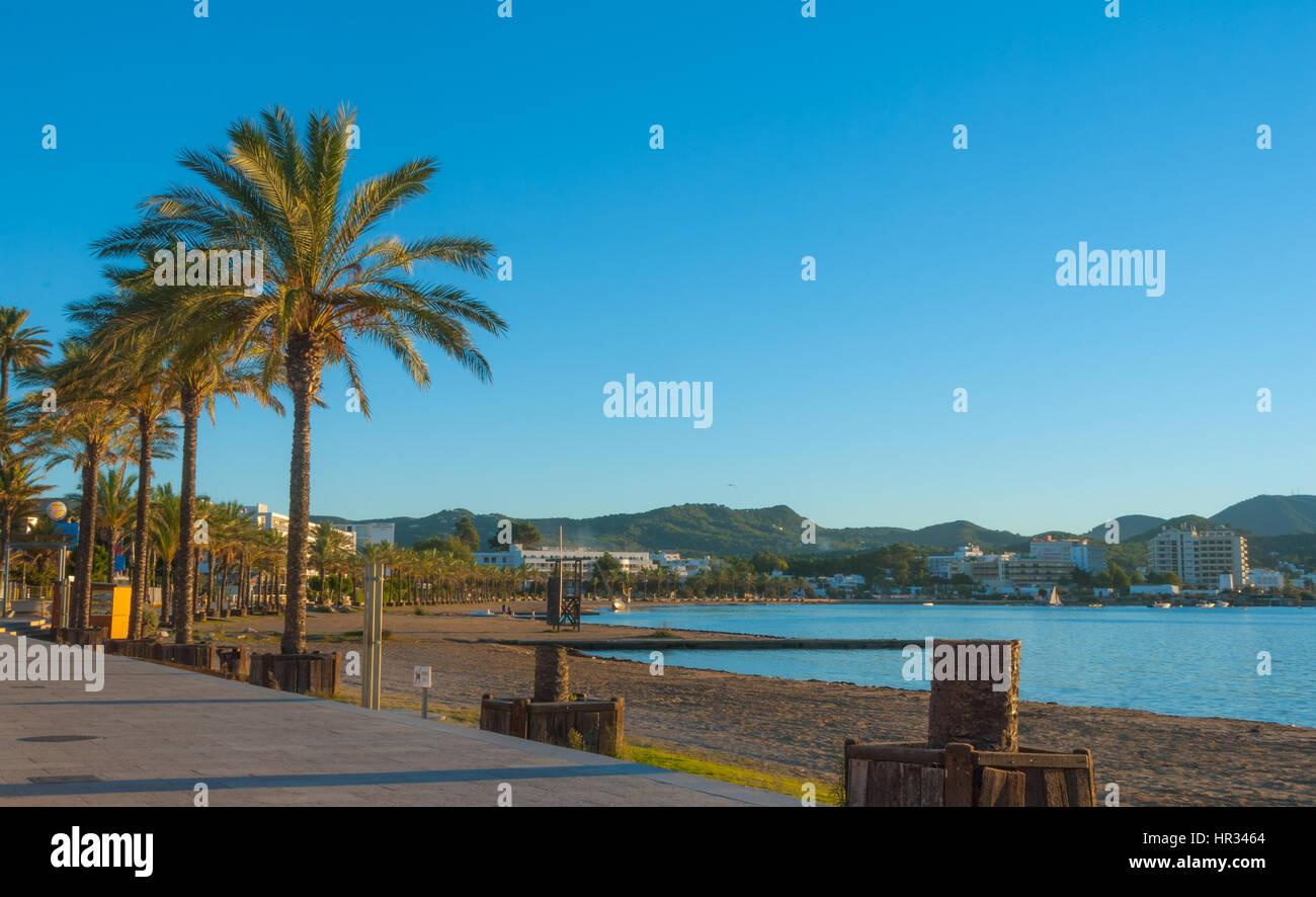 Late afternoon sun falls on beach, marina & boardwalk.  St Antoni de Portmany, Ibiza, Spain.  Empty beach & - Stock Image