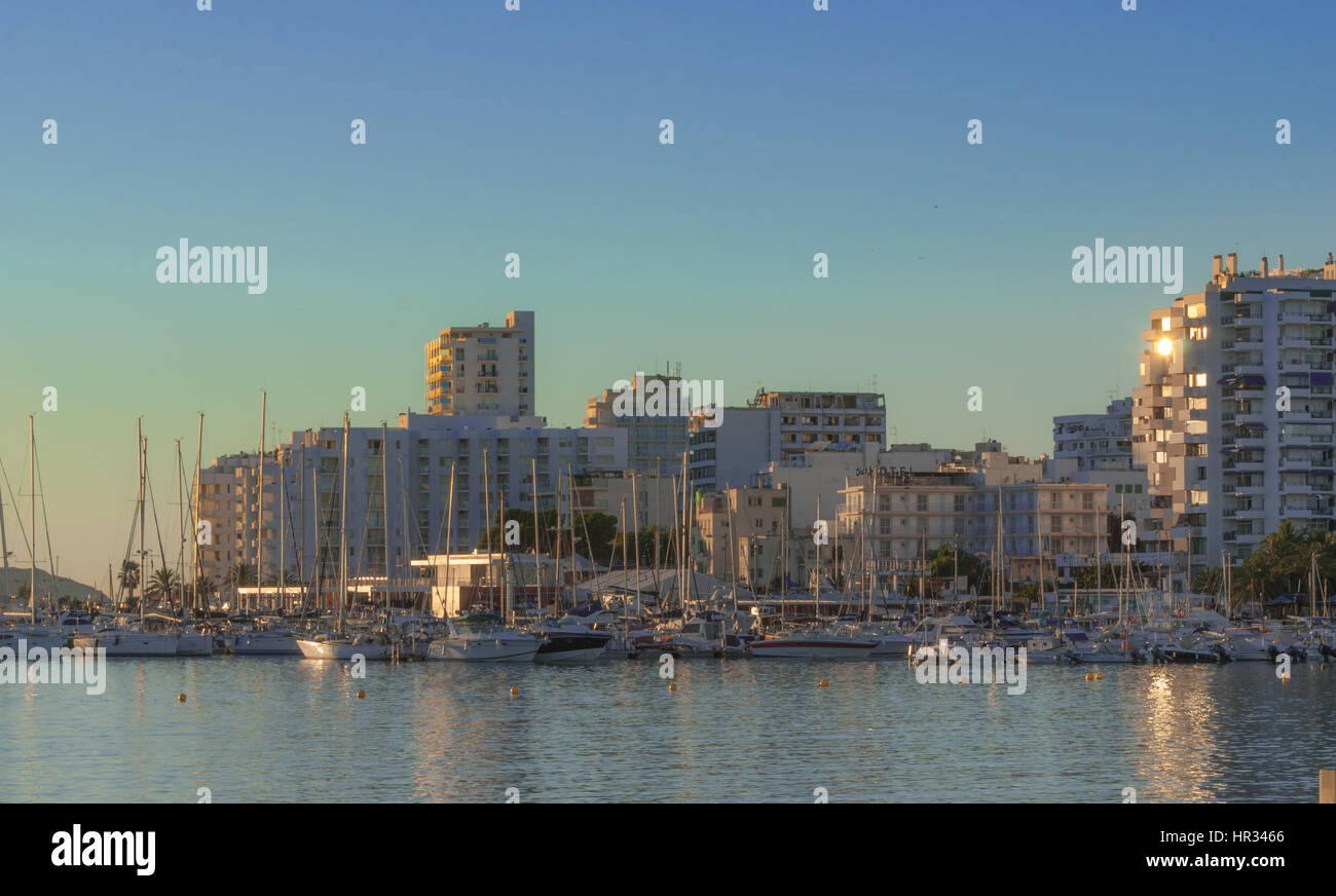 Late afternoon sun falls on marina boardwalk & bay in St Antoni de Portmany,  Ibiza,  Balearic Isl&s, Spain. - Stock Image