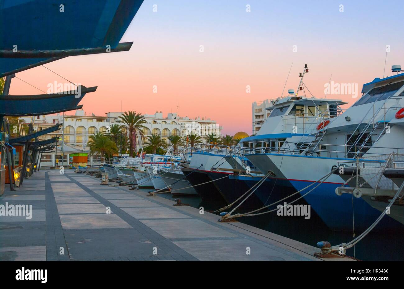 Boats in for the evening in marina harbor under dramatic magenta sunset color .  End of a warm sunny day in Ibiza, - Stock Image