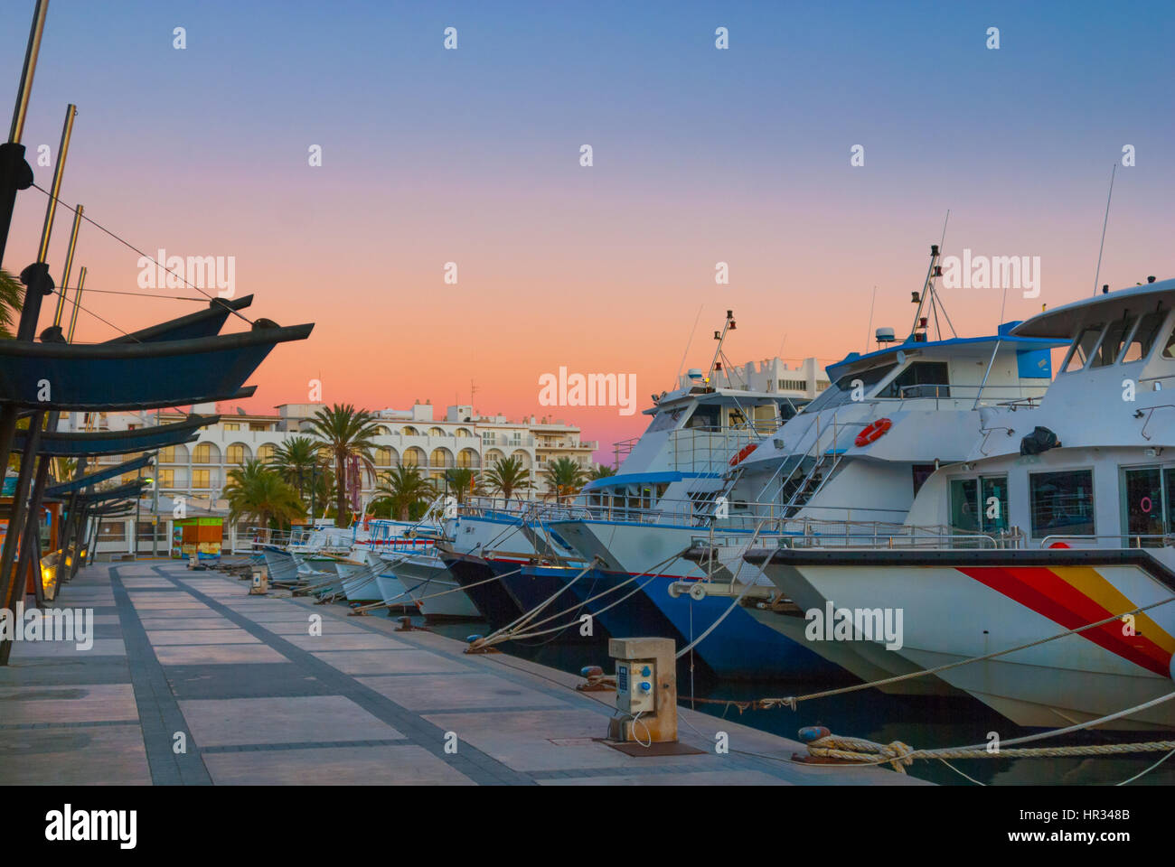 Boats in for the evening in marina harbor under dramatic magenta sunset color .  End of a warm sunny day in Ibiza, Stock Photo