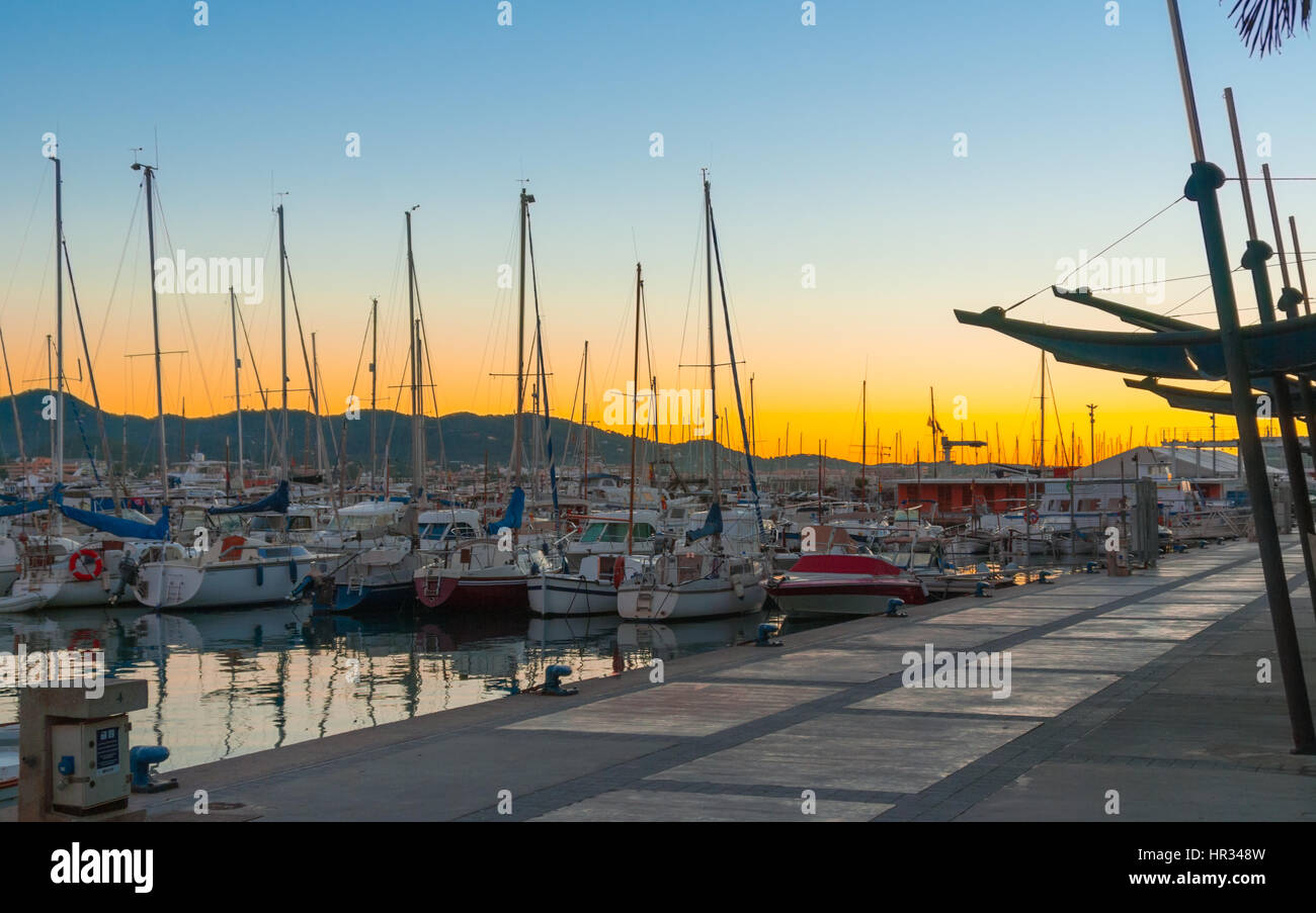 Magnificent golden sunset color in marina harbor.  End of a warm sunny day in Ibiza, St Antoni de Portmany, Spain. - Stock Image