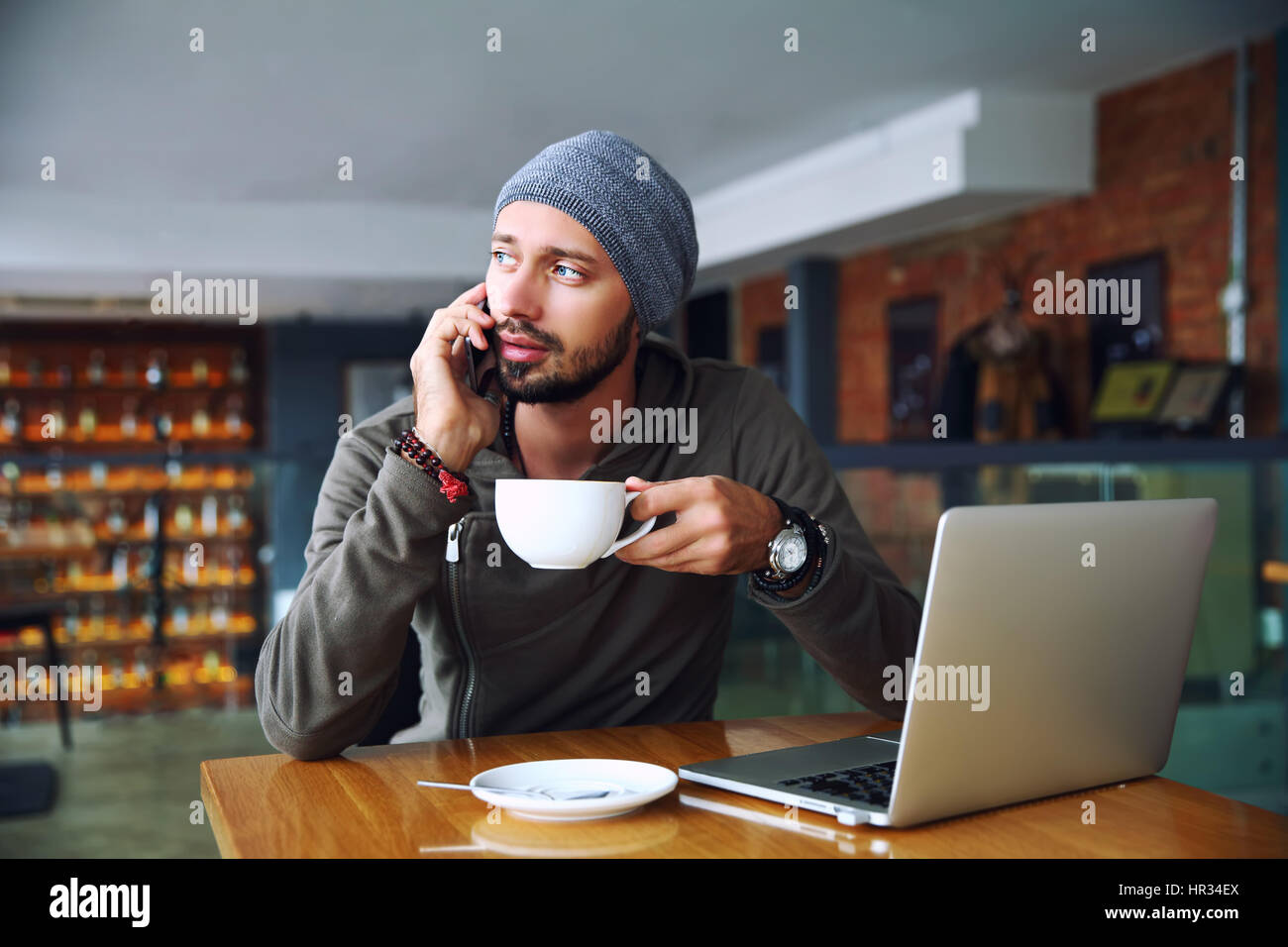 Young handsome hipster man with beard sitting in cafe talking mobile phone, holding cup of coffee. Laptop on wooden Stock Photo