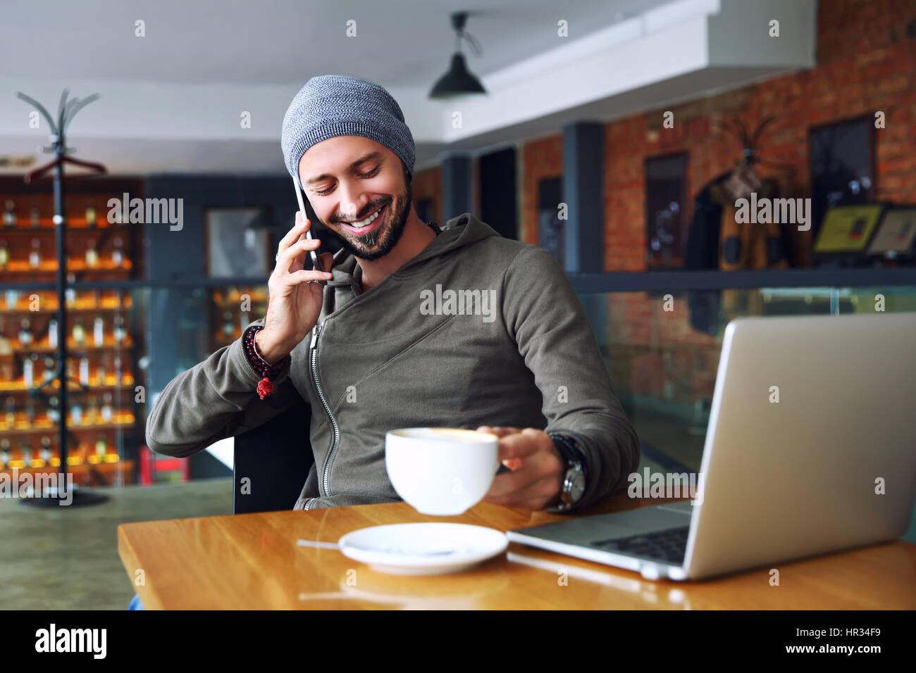 Young handsome hipster man with beard sitting in cafe talking mobile phone, holding cup of coffee and smiling. Laptop Stock Photo