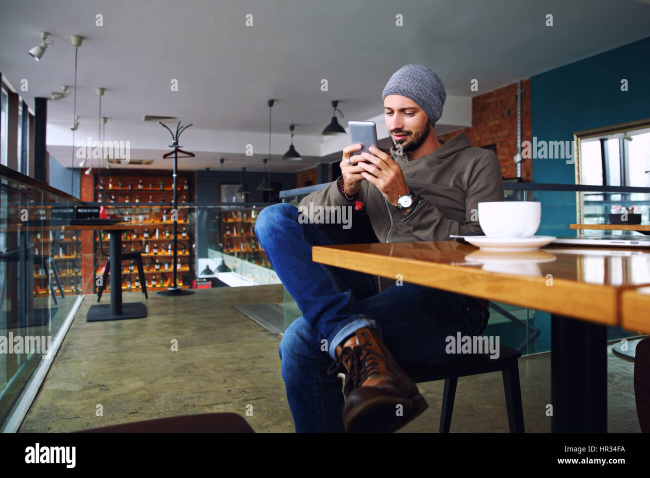 Young handsome hipster guy with beard texting with his mobile phone at the bar and having a cappuccino. - Stock Image