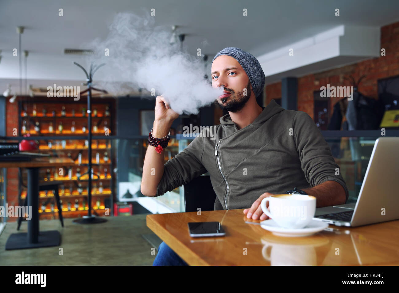 Young handsome hipster man with beard sitting in cafe with a cup of coffee, vaping and releases a cloud of vapor. Stock Photo