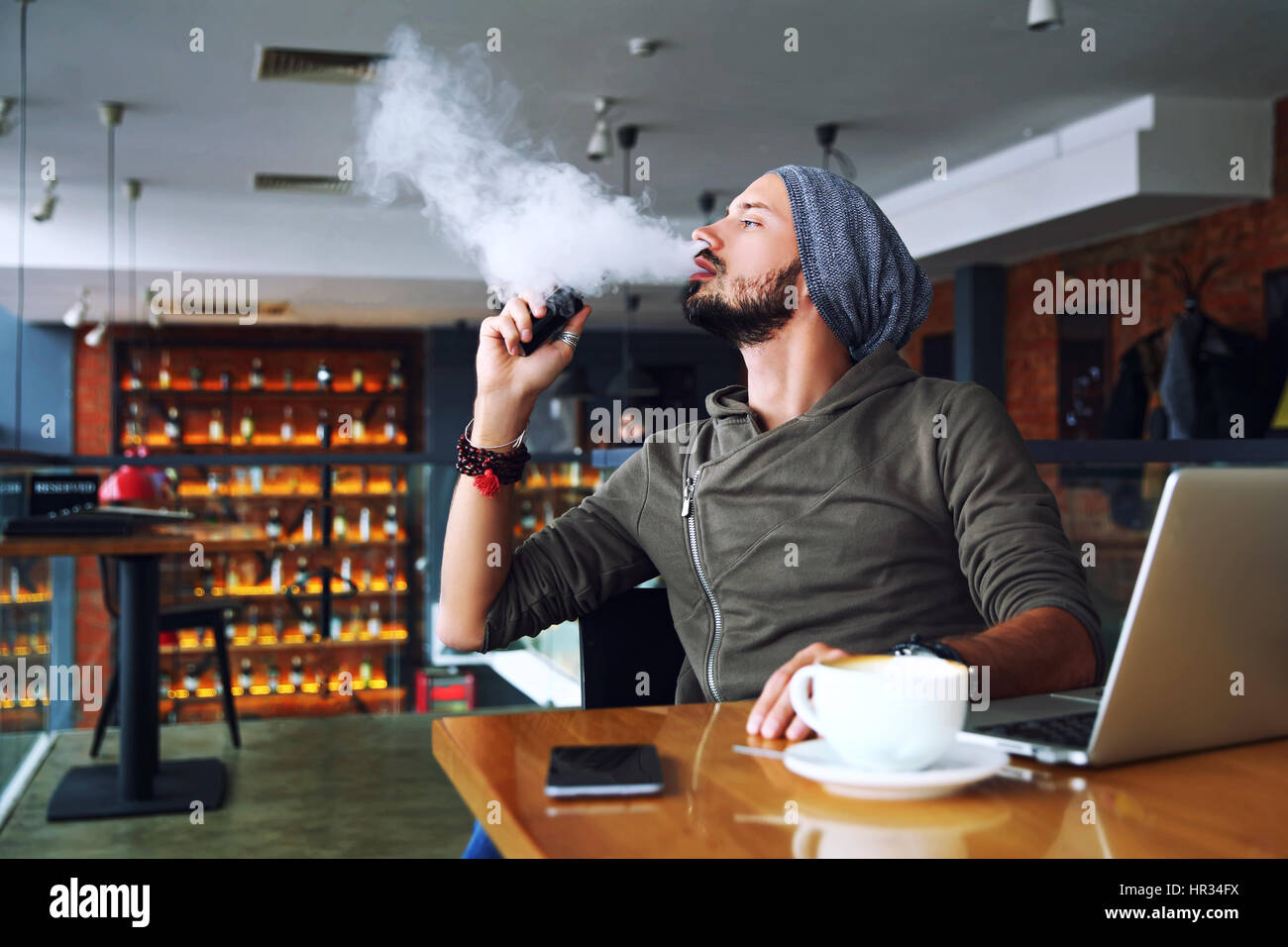 Young handsome hipster man with beard sitting in cafe with a cup of coffee, vaping and releases a cloud of vapor. - Stock Image