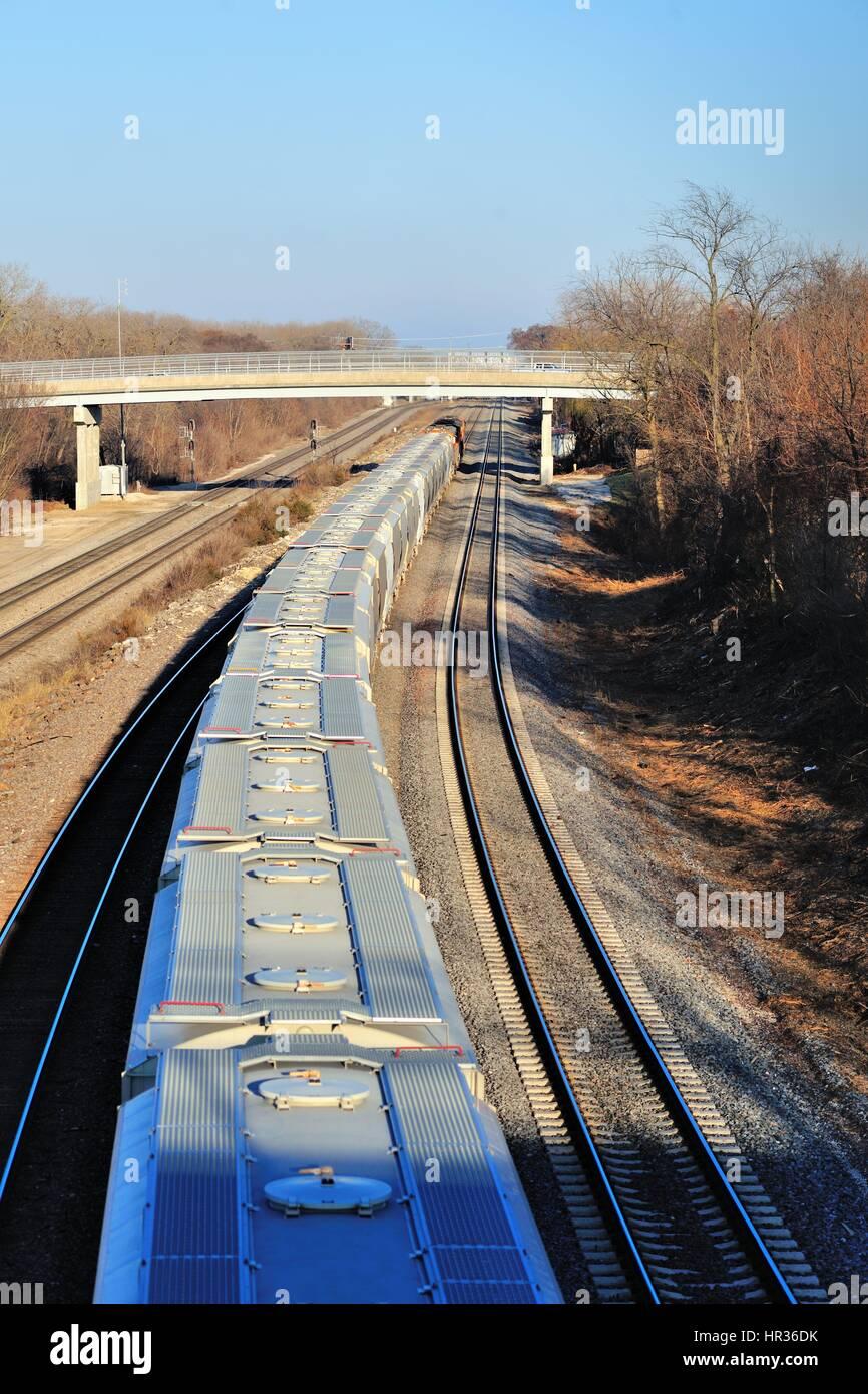 An eastbound Burlington Northern Santa Fe freight train heading along a three-tack mainline in Aurora, Illinois, - Stock Image