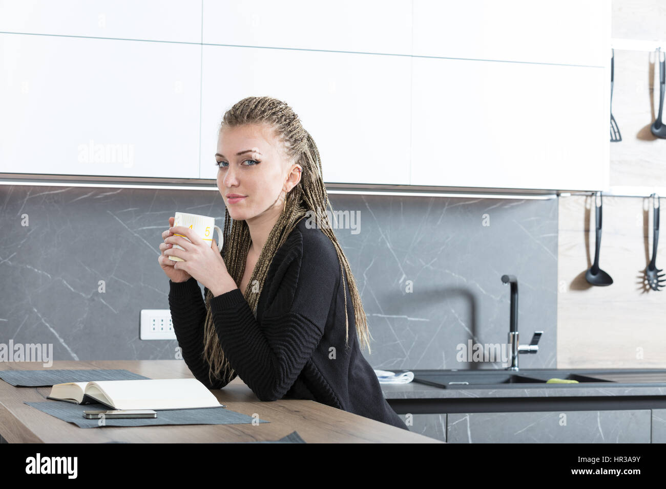 attractive woman having an hot drink while reading a book relaxing ...