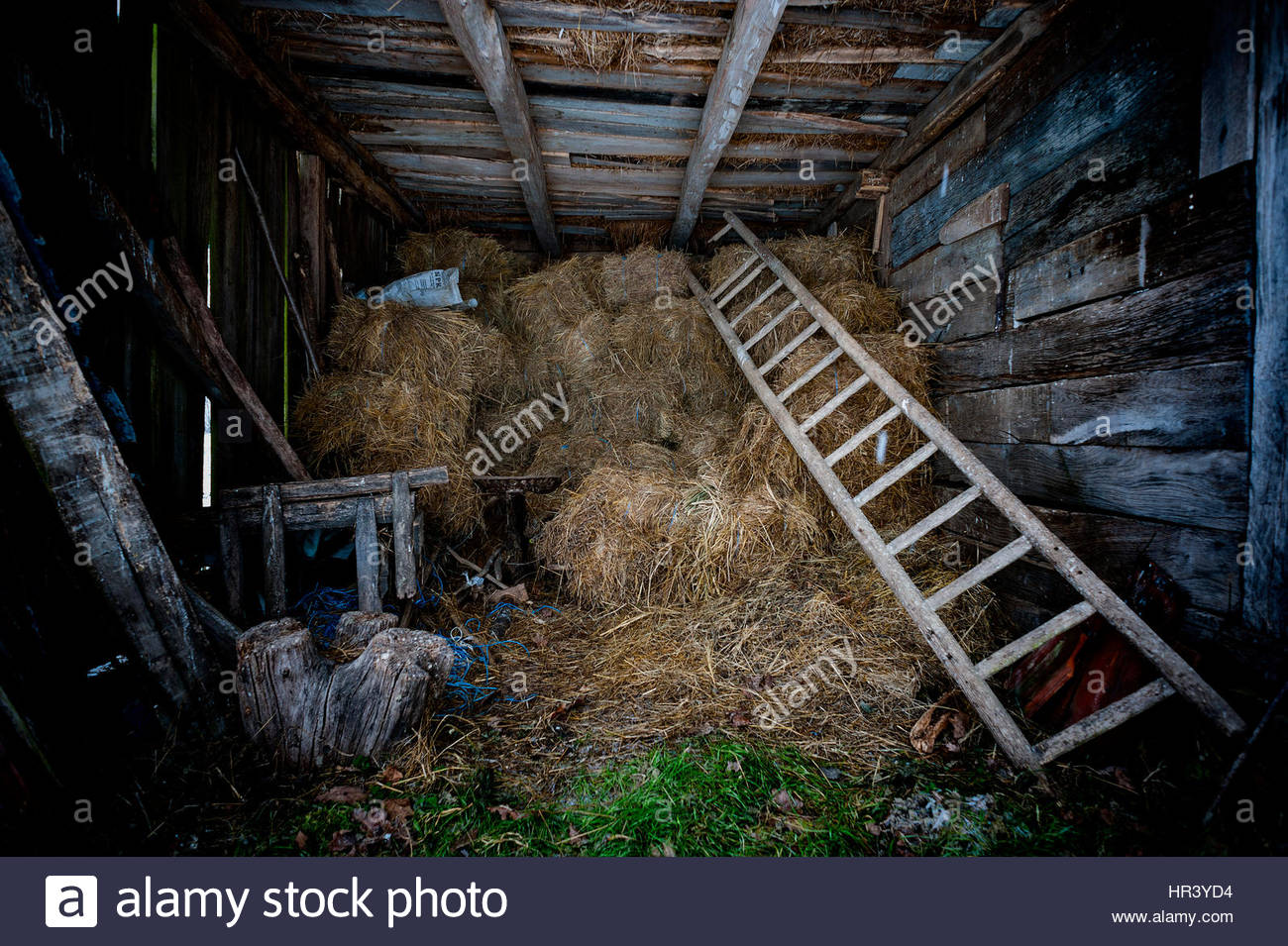 Interior Of Barn With Hay Bales Stacks And Tools