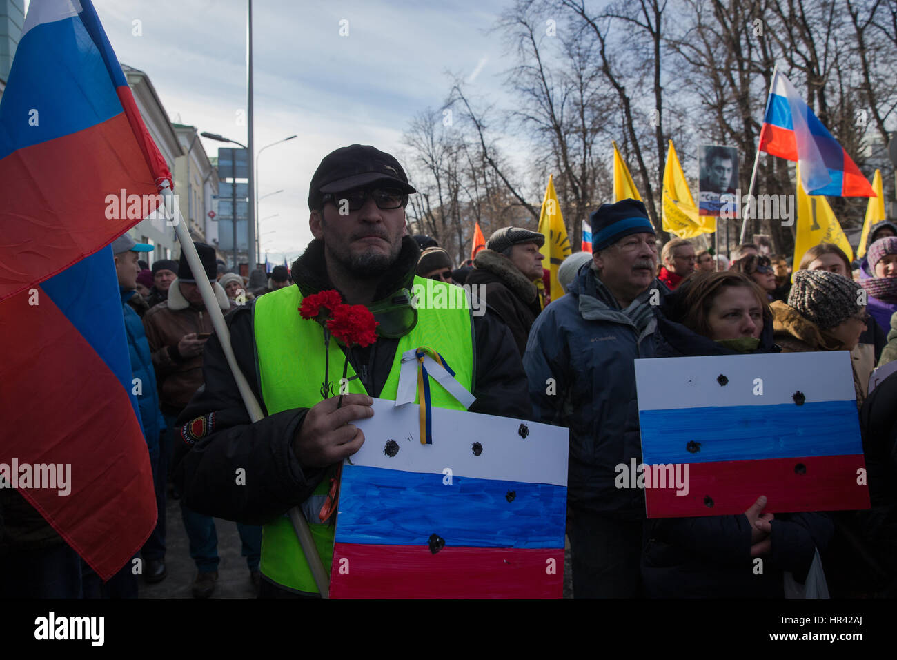 Moscow, Russia. 26th February 2017. A man holds Russian flags and flowers he takes part in a march in memory of Stock Photo