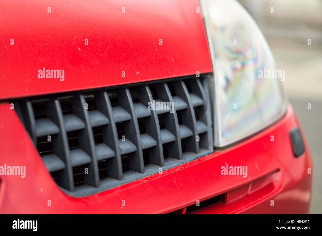 Faded plastic chequerboard grille on a Renault Clio. - Stock Image