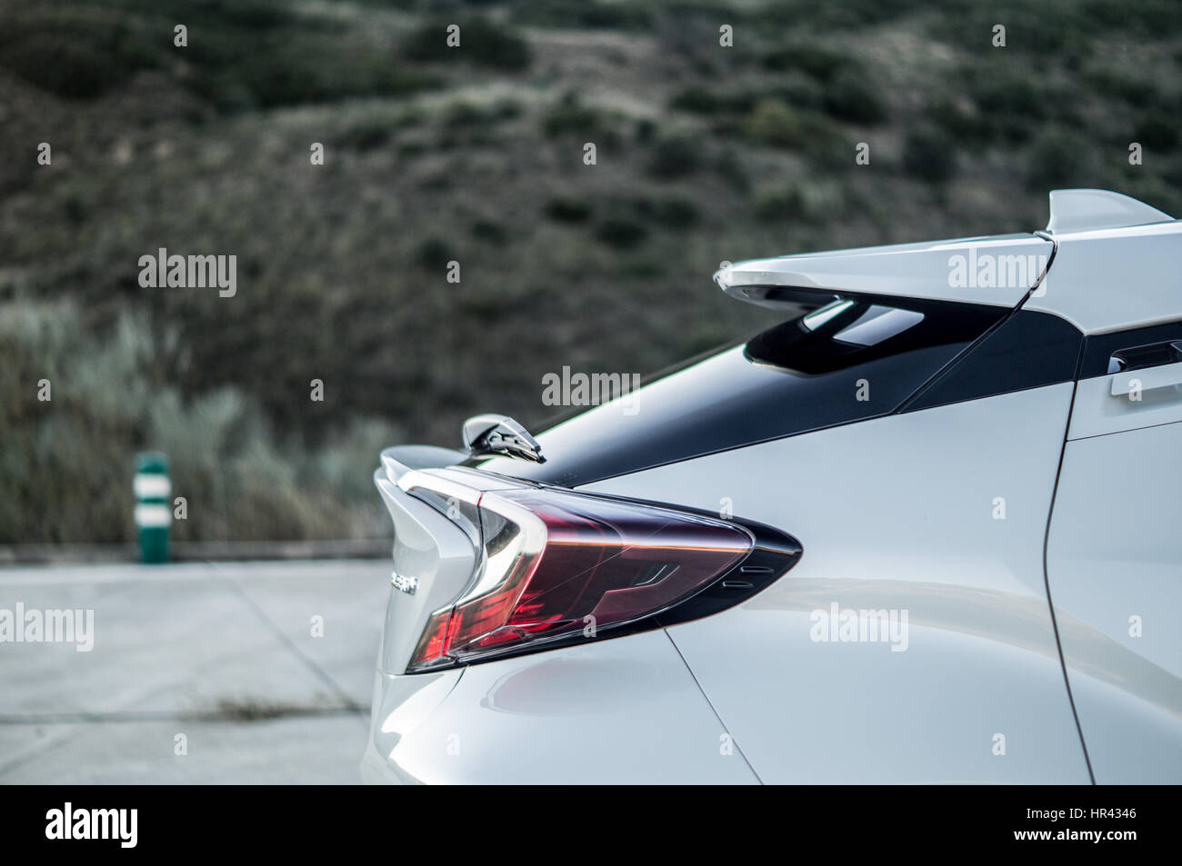 Rear wing and brake light of a white Toyota C-HR CHR on a helipad, hills and scenery in the background. - Stock Image