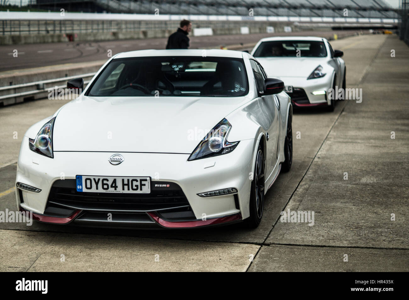 Good Two White Nissan 370z Nismo On A Race Track, In Pit Lane.   Stock