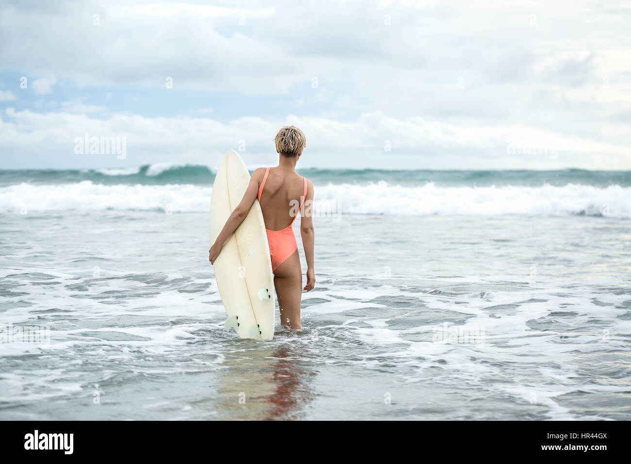 Blonde with surfboard on beach - Stock Image