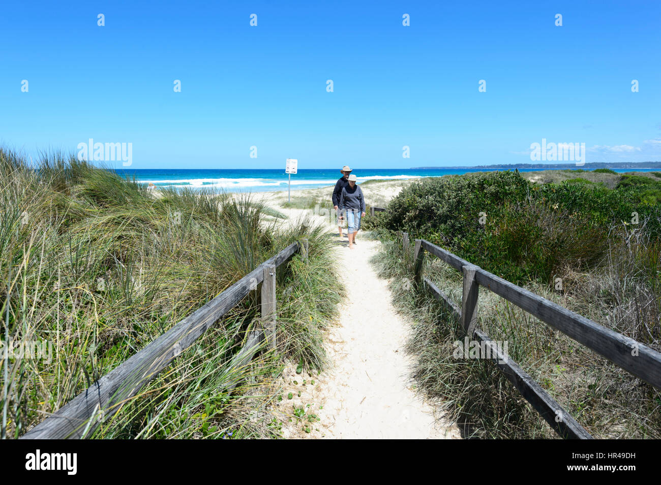 Two persons walking on the path to Conjola Beach, Shoalhaven, South Coast, New South Wales, NSW, Australia - Stock Image