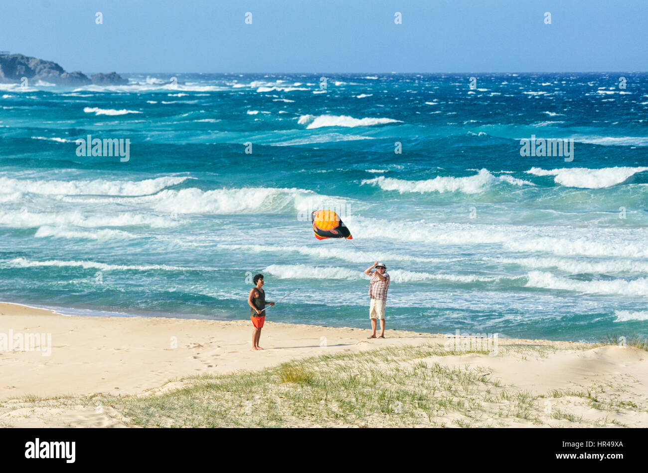 Two persons flying a kite on the beach, Potato Point, New South Wales, Australia - Stock Image