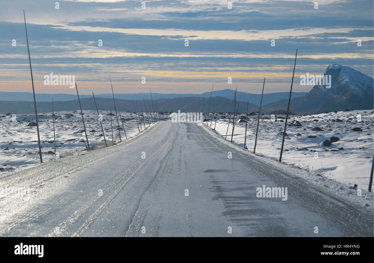 A gravel road with snow plow stakes in jotunheimen Norway - Stock Image