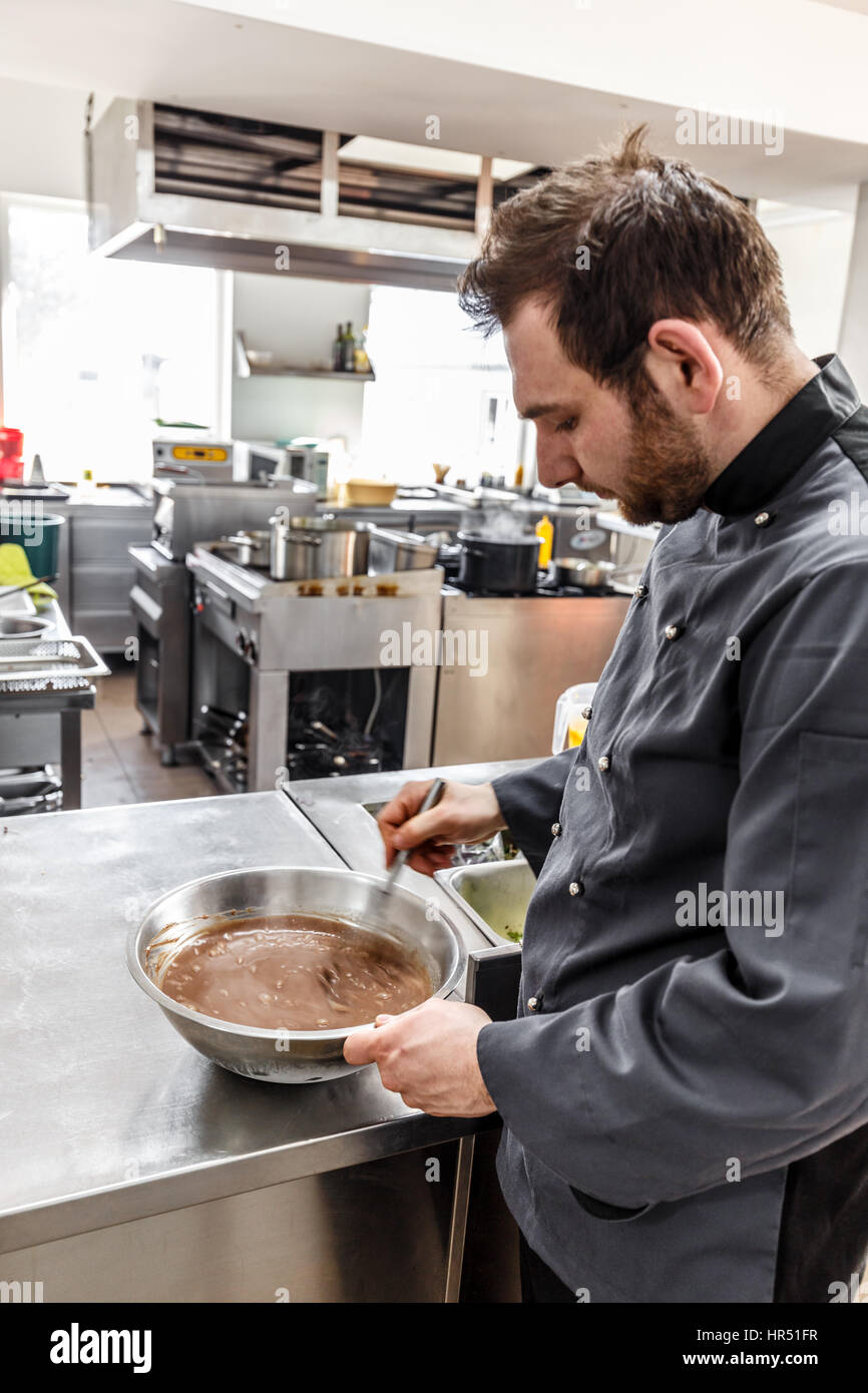 Young man chef in cook uniform making dessert in modern kitchen - Stock Image