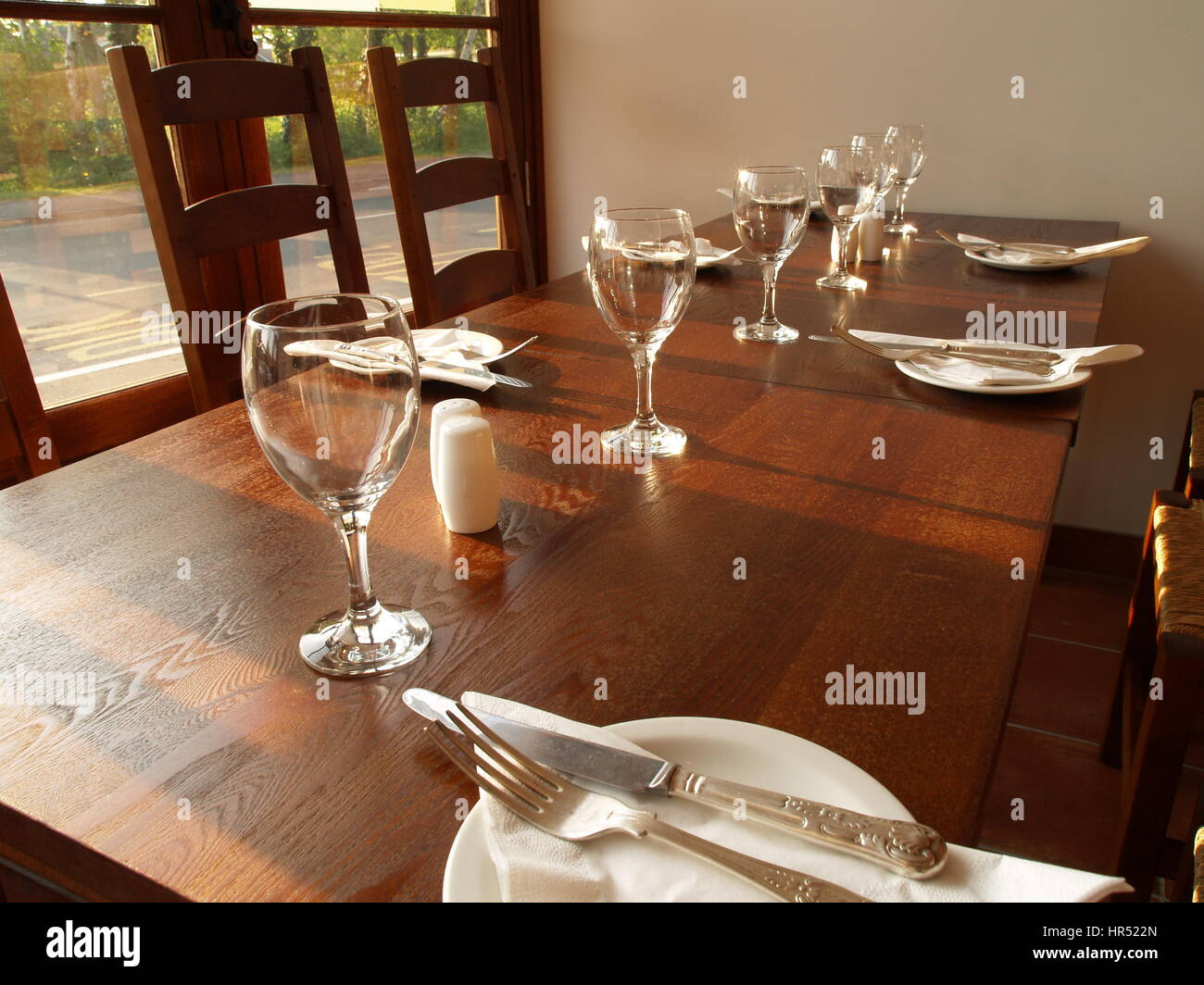 Table setting in a restaurant with wine glasses and side plates on a wooden table & Table setting in a restaurant with wine glasses and side plates on a ...