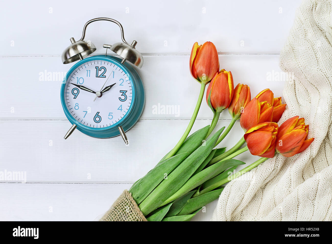 Alarm clock with a beautiful bouquet of tulips and a cozy blanket shot from above in a flatlay style over a wood - Stock Image